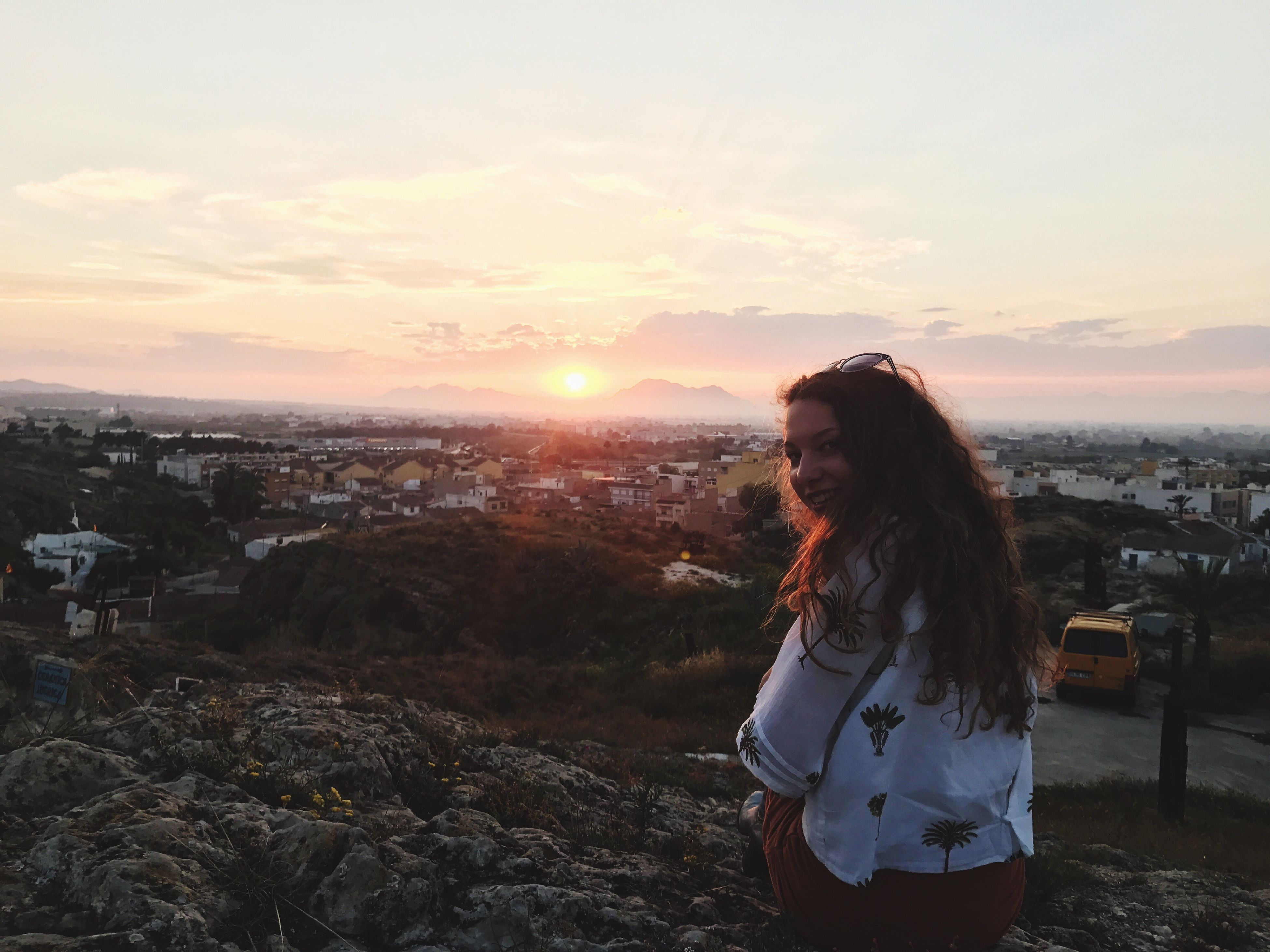 sky, sunset, lifestyles, cityscape, leisure activity, city, beauty in nature, real people, happiness, nature, one person, outdoors, scenics, young adult, beautiful woman, architecture, people, young women, only women, adults only, adult, day