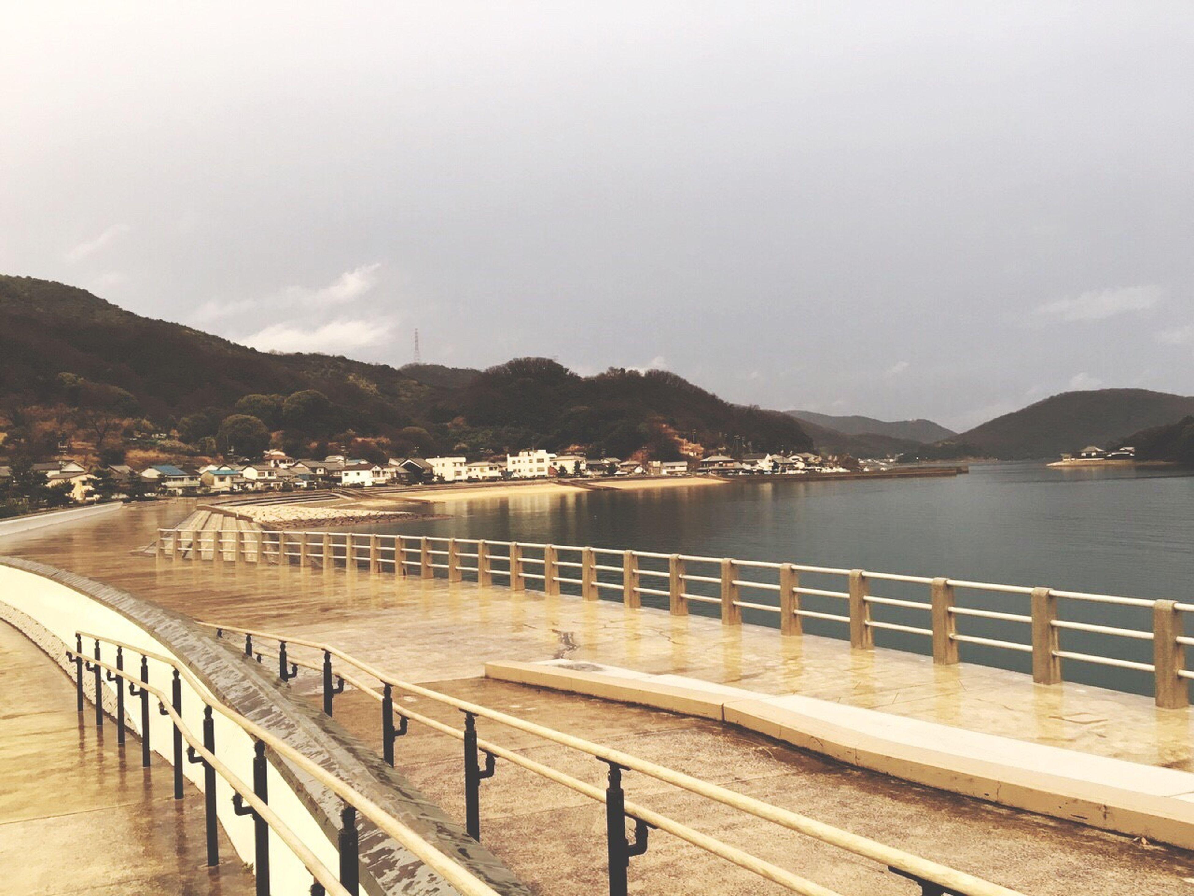 water, sea, mountain, railing, sky, pier, scenics, tranquil scene, tranquility, beauty in nature, nature, beach, mountain range, shore, built structure, cloud - sky, idyllic, jetty, outdoors, coastline