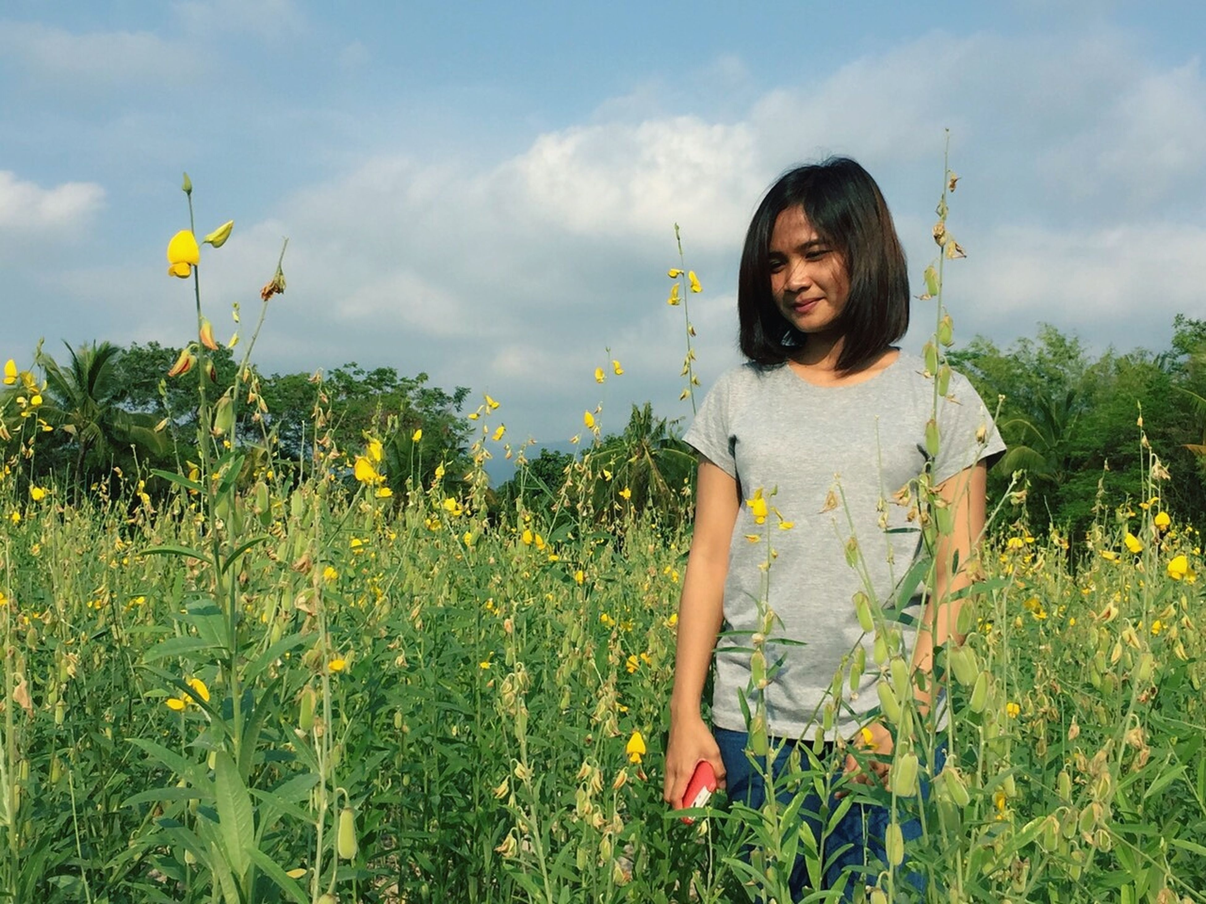 sky, person, young adult, leisure activity, lifestyles, grass, flower, field, standing, young women, casual clothing, growth, plant, cloud - sky, tree, smiling, nature, three quarter length