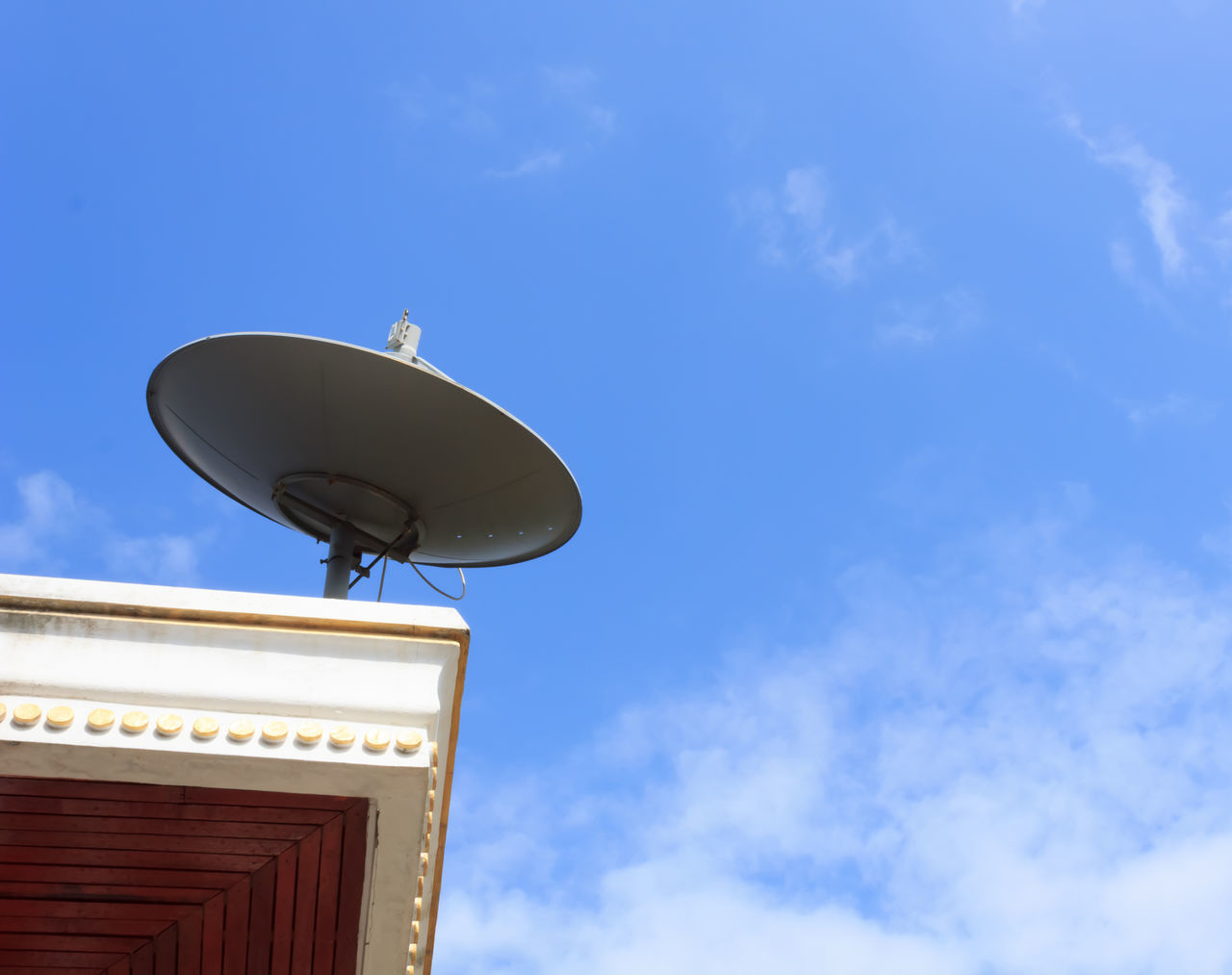 communication, satellite dish, global communications, broadcasting, low angle view, telecommunications equipment, technology, antenna - aerial, sky, architecture, built structure, day, cloud - sky, no people, roof, blue, building exterior, outdoors, data, wireless technology, television aerial, radar, information medium, radio station