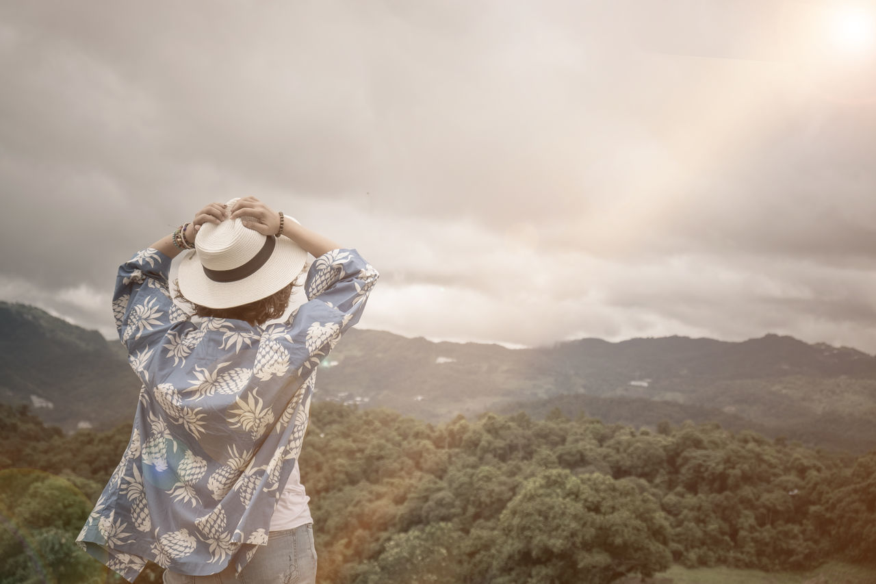 hat, mountain, sky, nature, outdoors, standing, cloud - sky, day, one person, scenics, landscape, real people, tranquility, beauty in nature, mountain range, tree, people