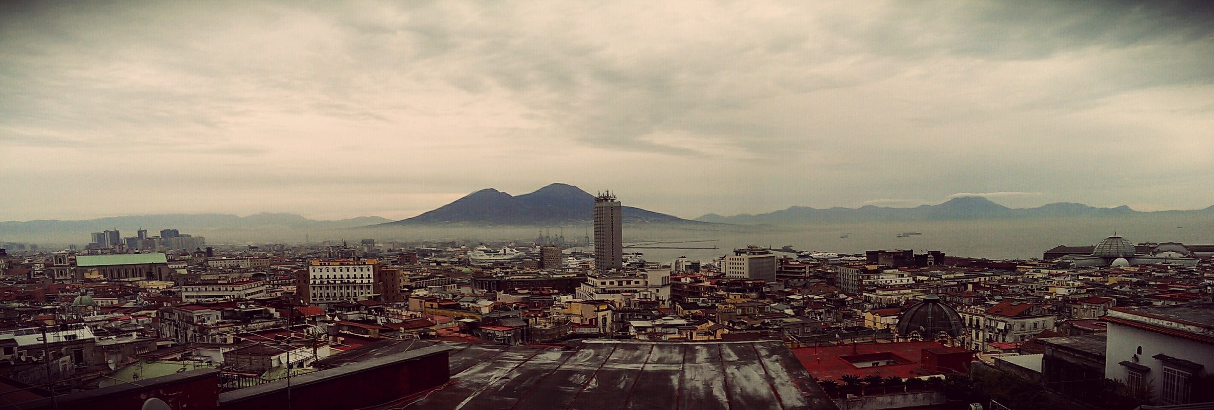 architecture, building exterior, built structure, cityscape, city, sky, cloud - sky, high angle view, crowded, residential district, cloudy, residential building, residential structure, mountain, cloud, city life, outdoors, road, no people, day
