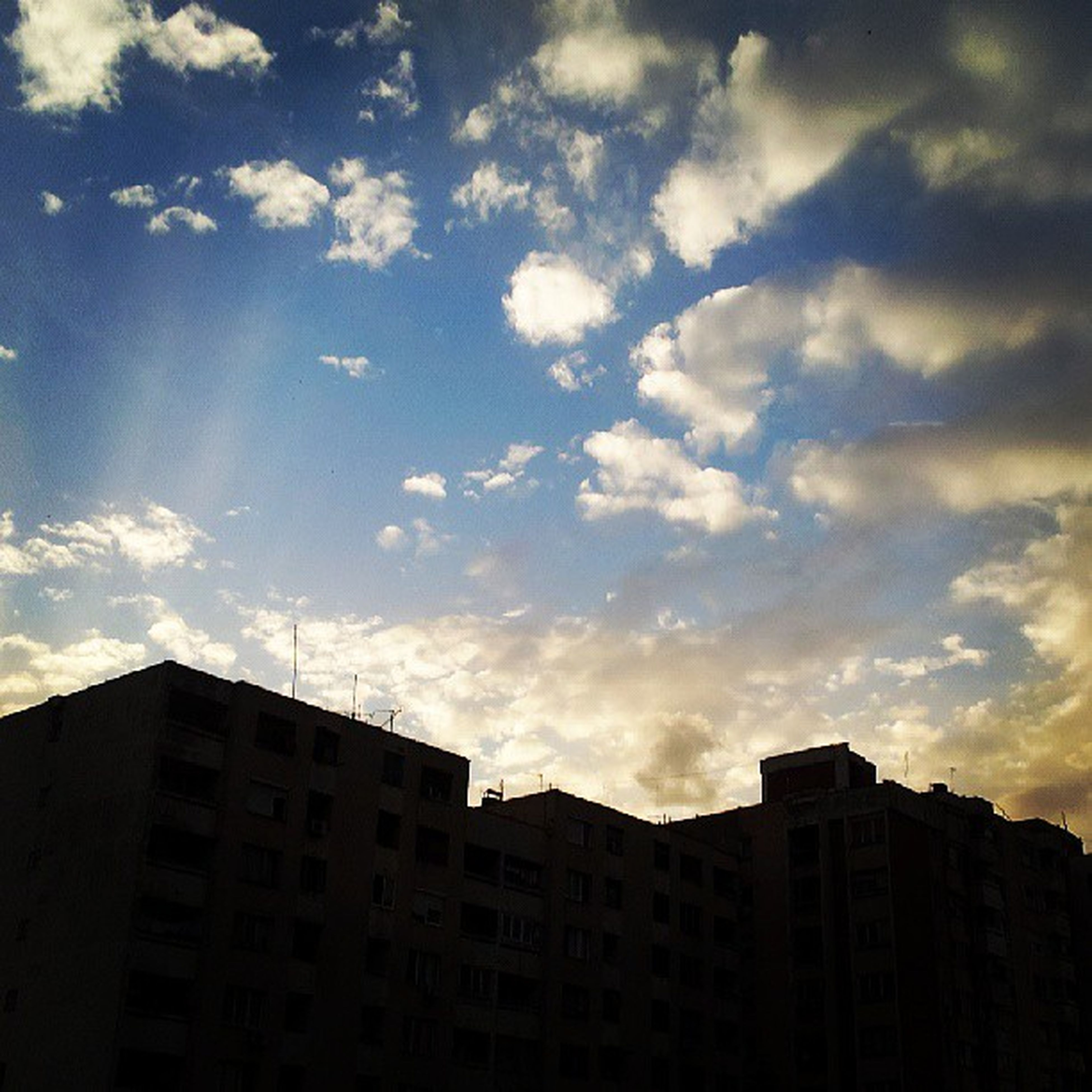architecture, building exterior, built structure, low angle view, sky, cloud - sky, building, city, cloud, cloudy, residential building, residential structure, high section, silhouette, window, outdoors, no people, sunset, house, day