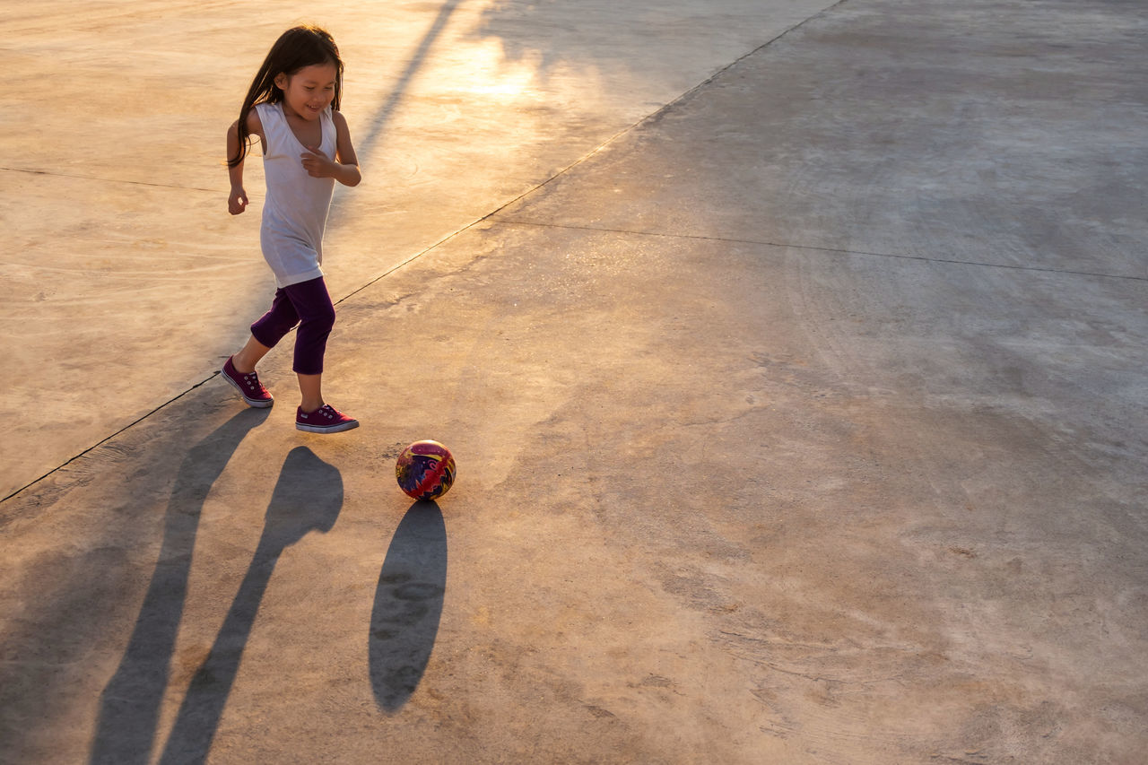 Ball Brown Hair Casual Clothing Childhood Competitive Sport Concrete Floor Court Day Full Length Leisure Games Motion One Girl Only One Person Outdoors People Playing Real People Run Skateboard Park Skill  Soccer Sport Sports Activity Sunlight Young Adult