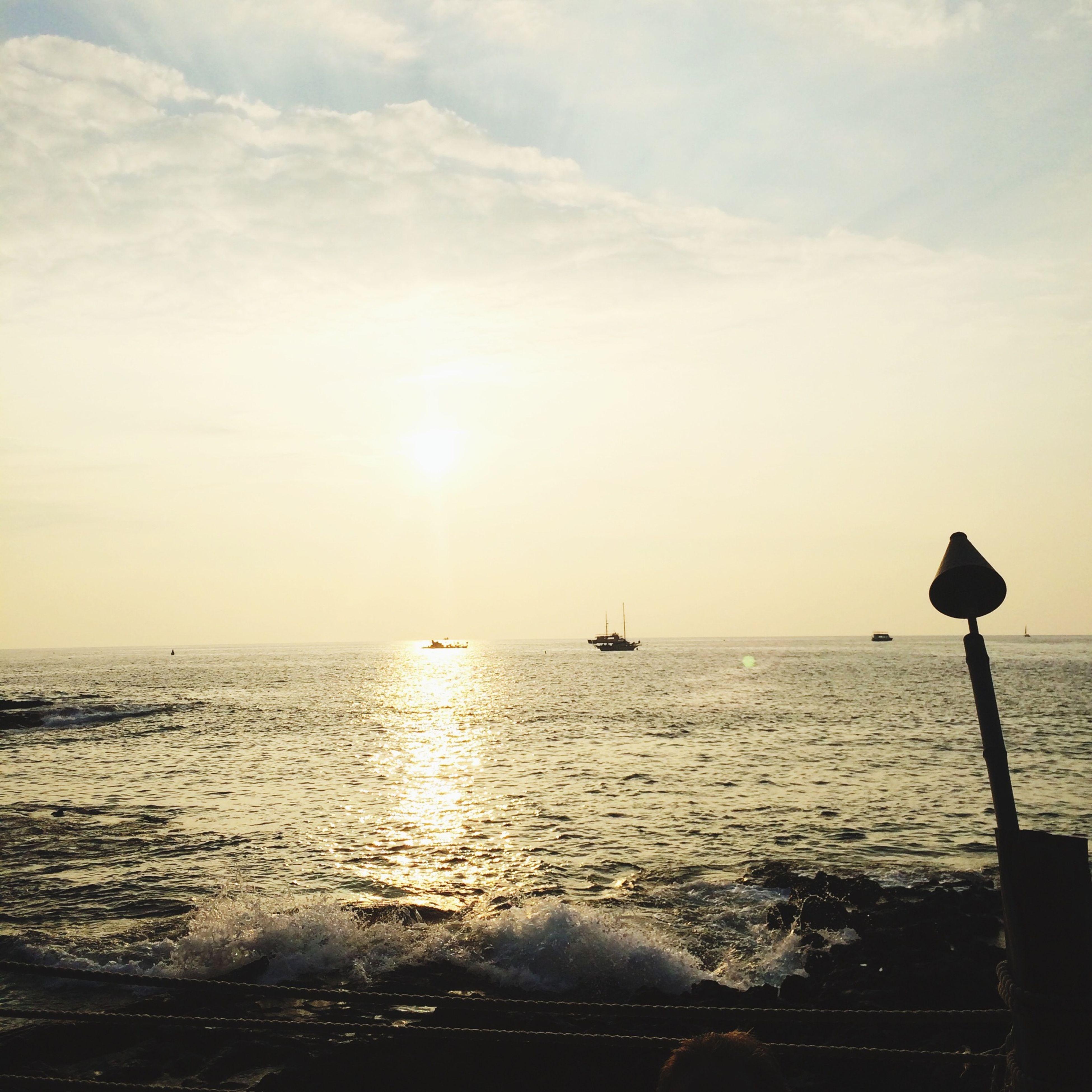 sea, water, horizon over water, sun, nautical vessel, sunset, transportation, scenics, tranquil scene, tranquility, sky, beauty in nature, boat, mode of transport, sunlight, nature, rippled, idyllic, reflection, sunbeam