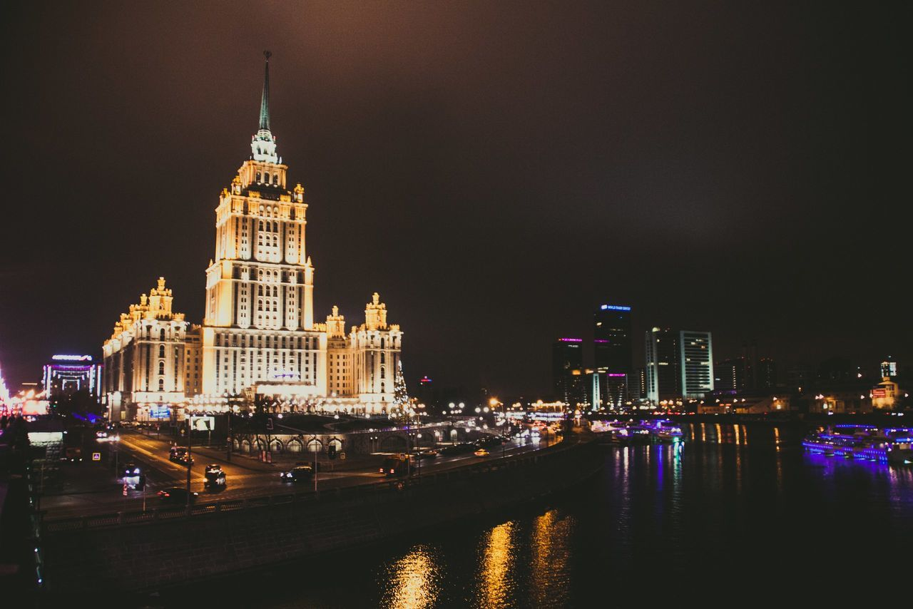 architecture, illuminated, building exterior, built structure, night, travel destinations, waterfront, city, water, sky, river, outdoors, skyscraper, cityscape, no people