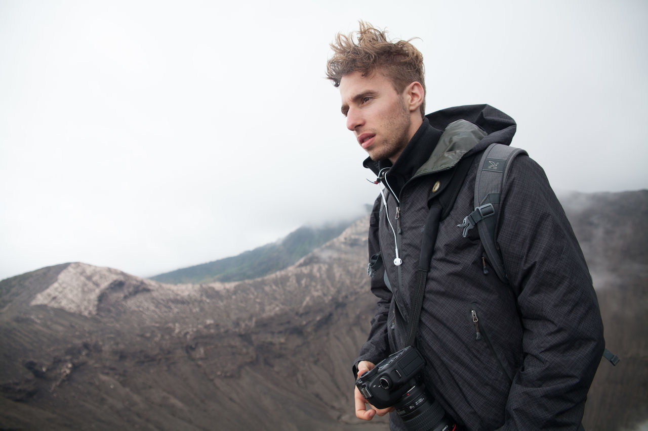 real people, leisure activity, one person, young men, jacket, young adult, casual clothing, standing, mountain, lifestyles, outdoors, day, hiking, nature, beauty in nature, camera - photographic equipment, technology, warm clothing, sky, people