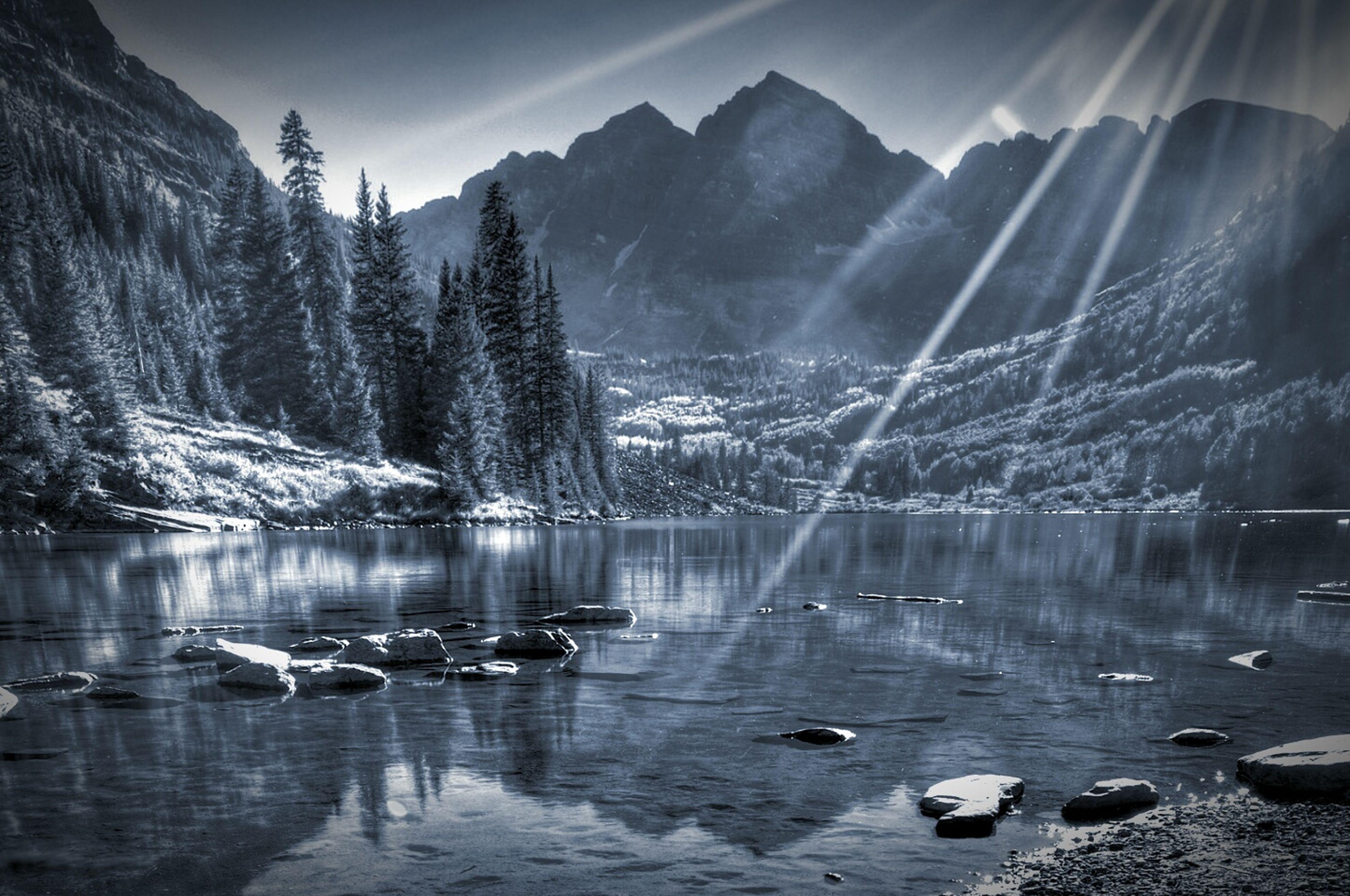 water, mountain, reflection, lake, tranquil scene, scenics, tranquility, beauty in nature, nature, mountain range, sky, sun, sunlight, river, idyllic, tree, rock - object, waterfront, sunbeam, outdoors