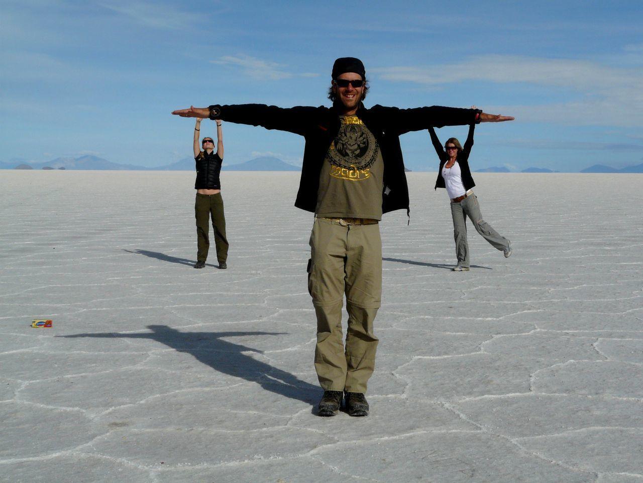 Optical illusion of women hanging on man arms in white desert