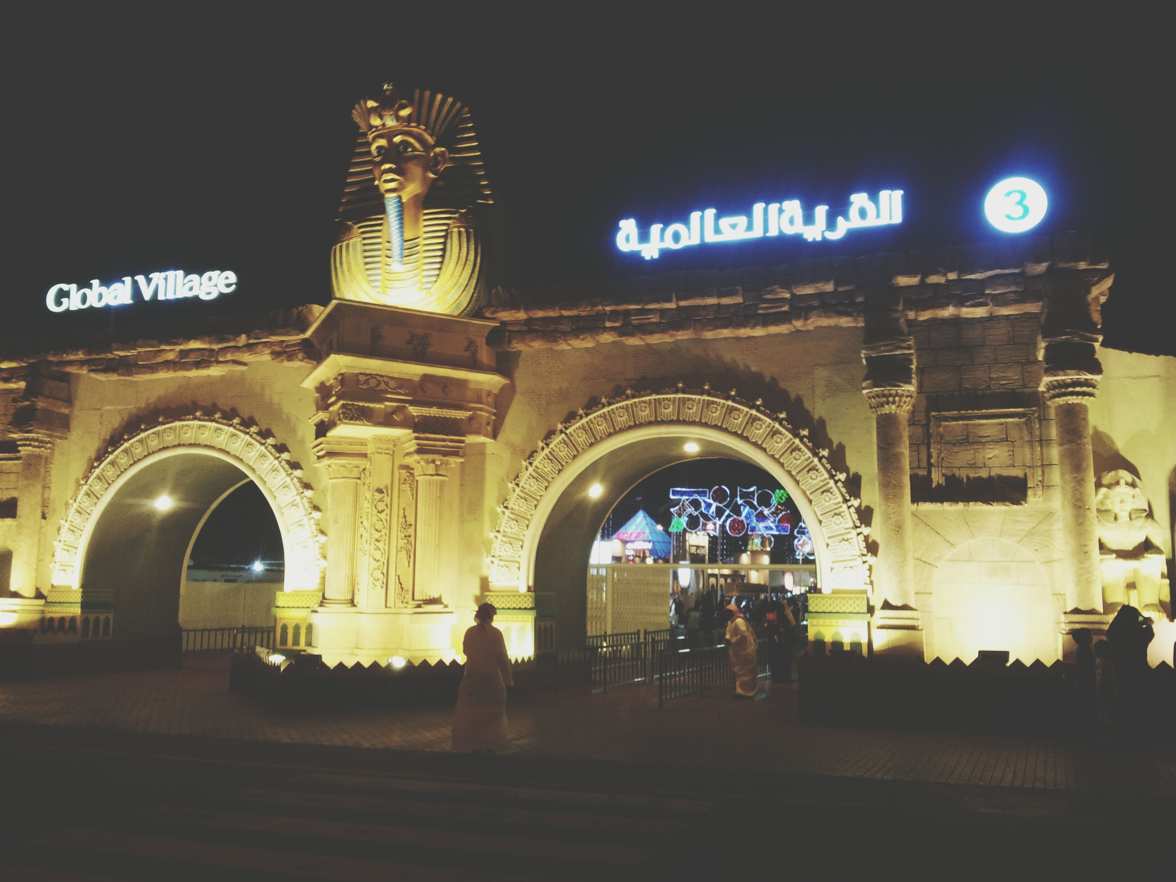 arch, architecture, night, illuminated, text, built structure, men, building exterior, western script, lifestyles, transportation, communication, person, walking, travel, leisure activity, city life, clear sky, city