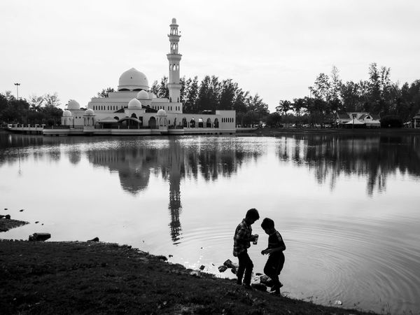 Two boys playing by the lake with a mosque and its reflection in the background Architecture Black And White Boys Day Floating Mosque Kuala Terengganu Lake Lakeside Masjid Masjid Tengku Tengah Zaharah Minaret Monochrome Photography Mosque Outdoors Playing Reflection Reflections Silhouette Two Two Boys Two People Water The Street Photographer - 2017 EyeEm Awards