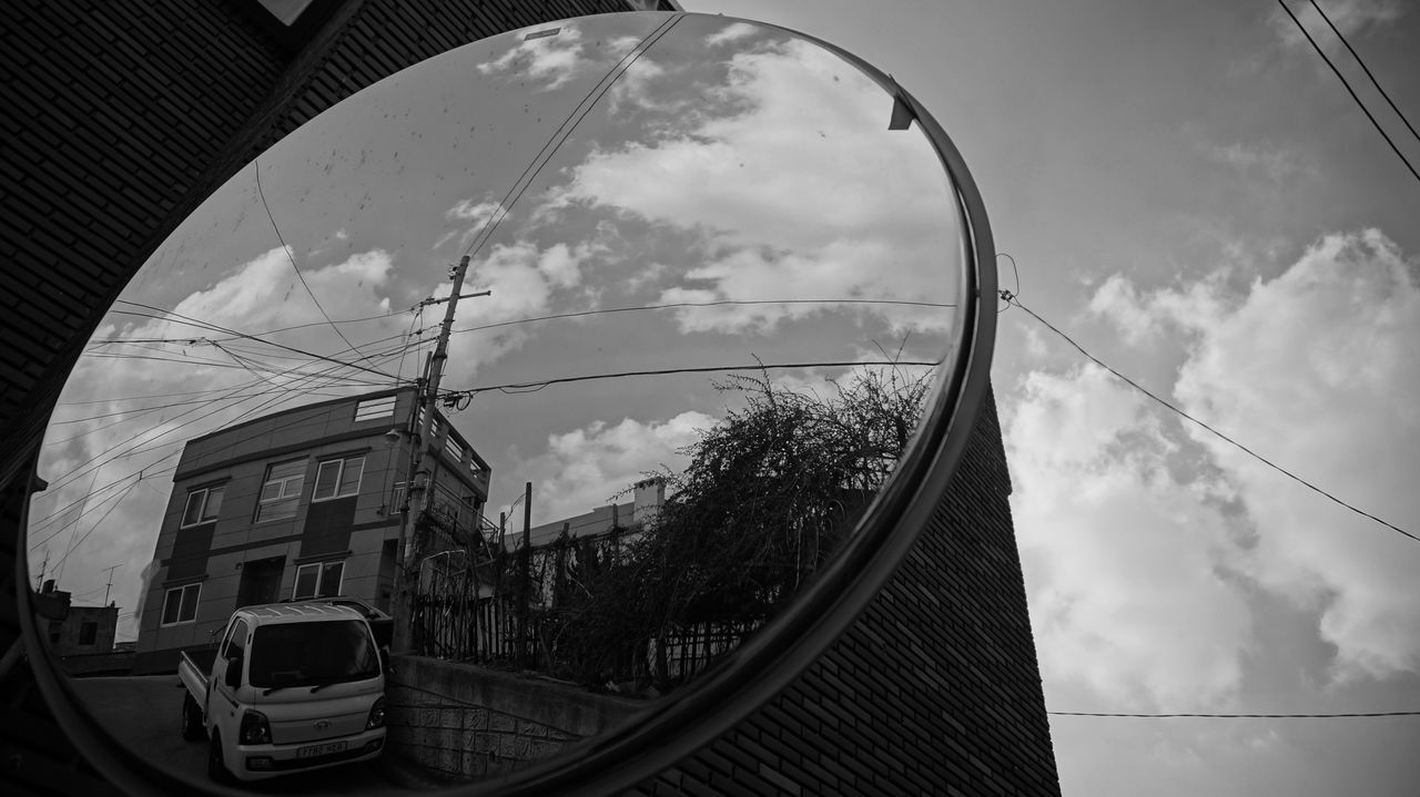 sky, cloud - sky, cloudy, cloud, built structure, low angle view, architecture, transportation, day, circle, fish-eye lens, no people, glass - material, weather, connection, outdoors, building exterior, mode of transport, reflection, arch