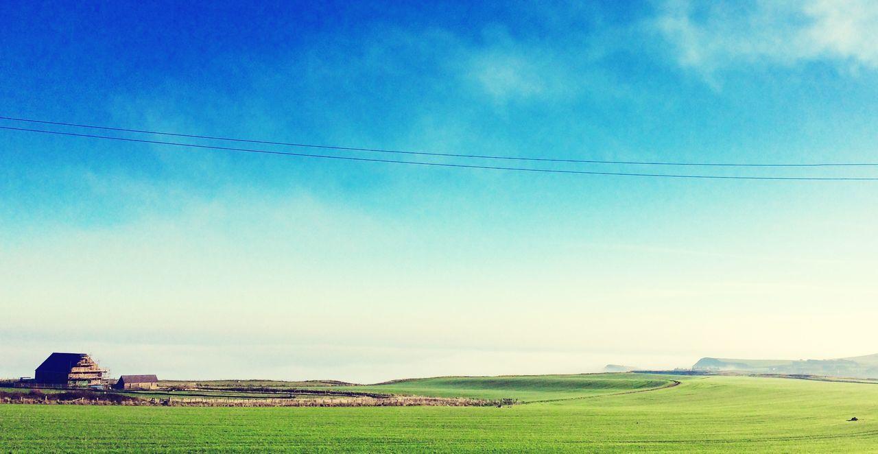 Cottage On Green Landscape Against Sky