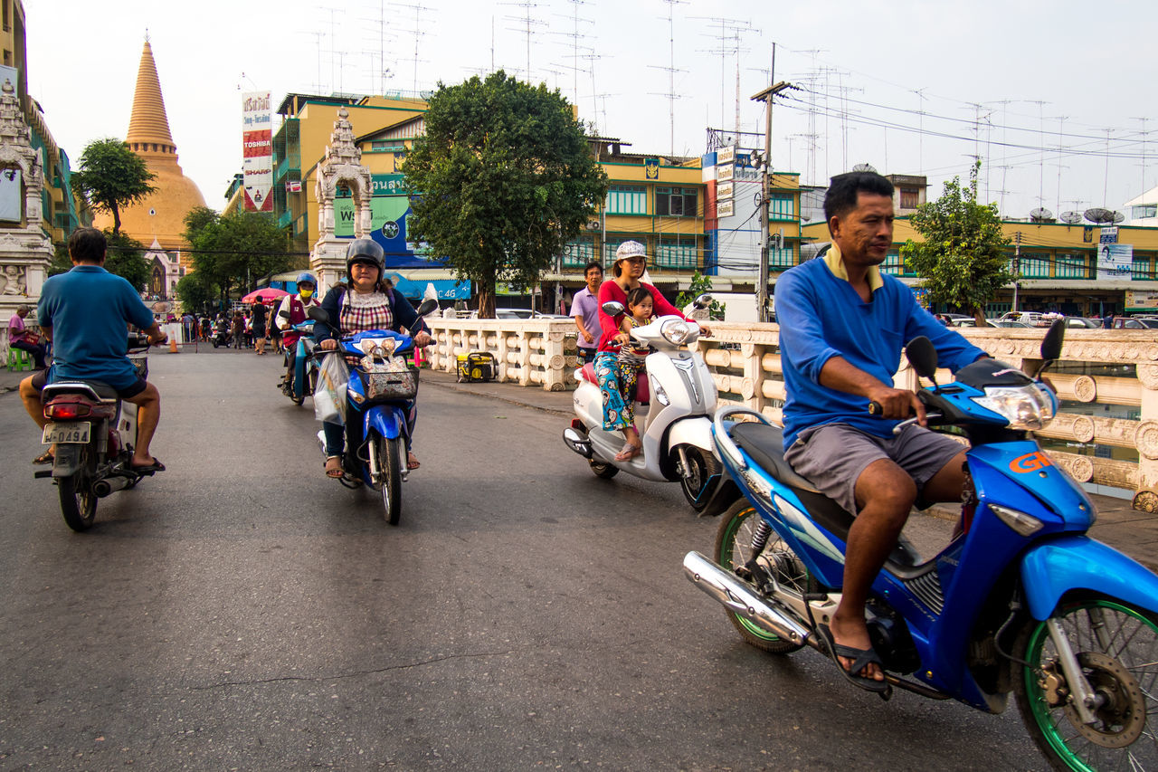 bicycle, transportation, real people, mode of transport, land vehicle, riding, cycling, built structure, large group of people, building exterior, architecture, men, leisure activity, lifestyles, day, outdoors, road, city, sitting, motorcycle, women, group of people, full length, tree, biker, young adult, people