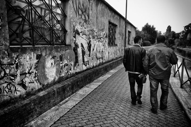 Naviglio della Martesana, Milano, Italy Architecture Black & White Black And White Built Structure Canal Day EyeEm Gallery Friendship Full Length Graffiti Horizontal Lifestyles Outdoors Rear View River Walking Wall Window Windows