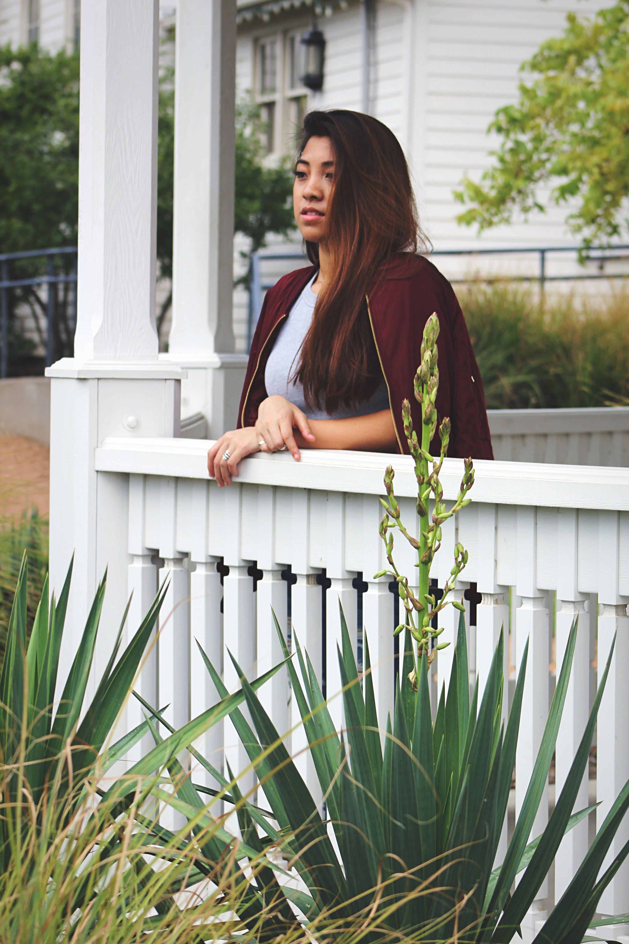 young women, young adult, person, lifestyles, leisure activity, long hair, casual clothing, plant, sitting, beauty, focus on foreground, full length, flower, nature, growth, outdoors, confidence, day