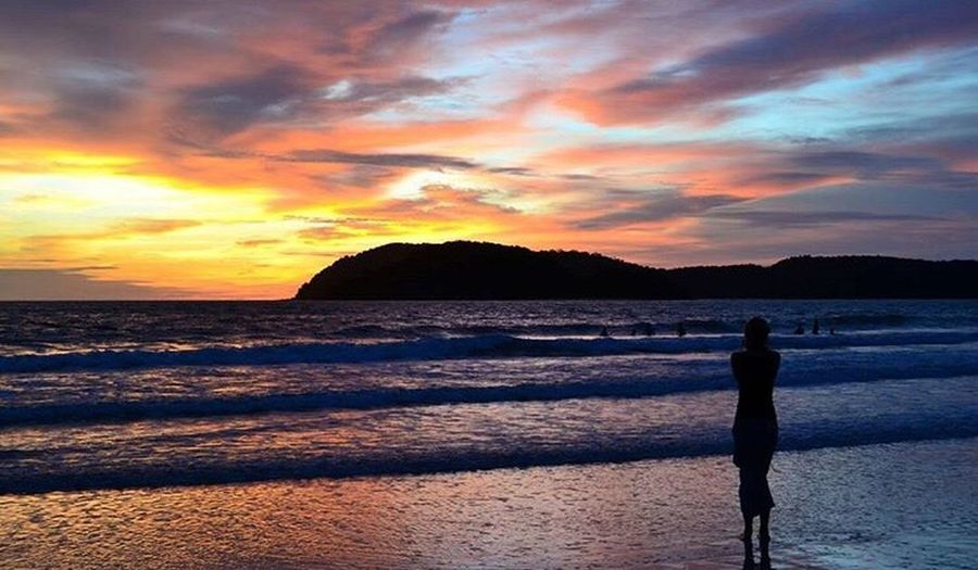 Sunset Sea Silhouette Beauty In Nature Scenics Beach Nature Water Sky One Person Standing Cloud - Sky Tranquil Scene Full Length Tranquility Real People Horizon Over Water Outdoors People Wave