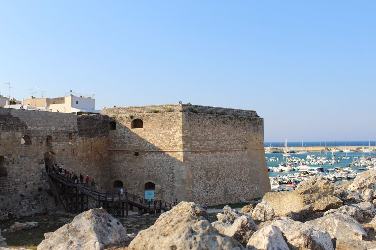 built structure, architecture, building exterior, fort, clear sky, history, day, castle, copy space, sea, outdoors, no people, water, nature, sunlight, travel destinations, sky