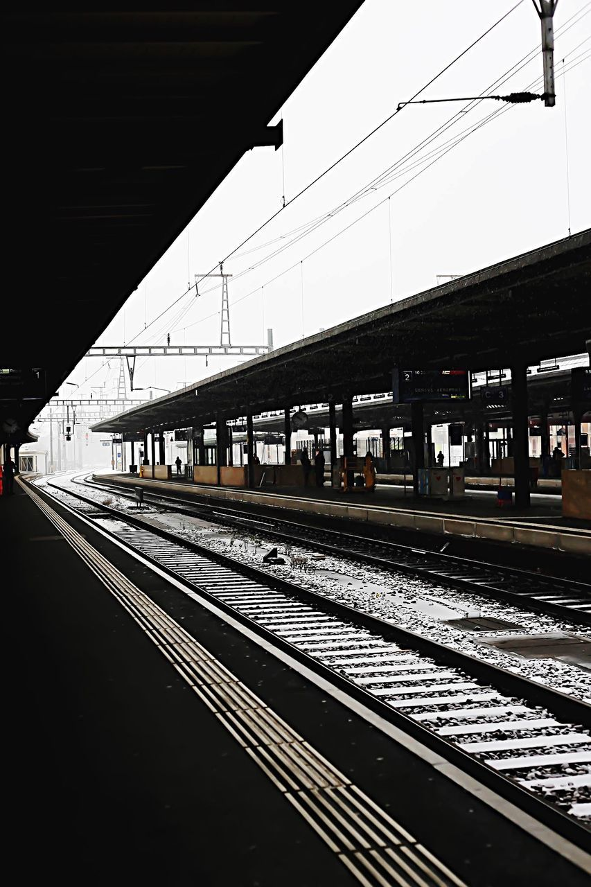 transportation, railroad track, rail transportation, public transportation, cable, railroad station, railroad station platform, power line, railway track, connection, train - vehicle, sky, day, no people, railway, electricity pylon, outdoors, clear sky, architecture