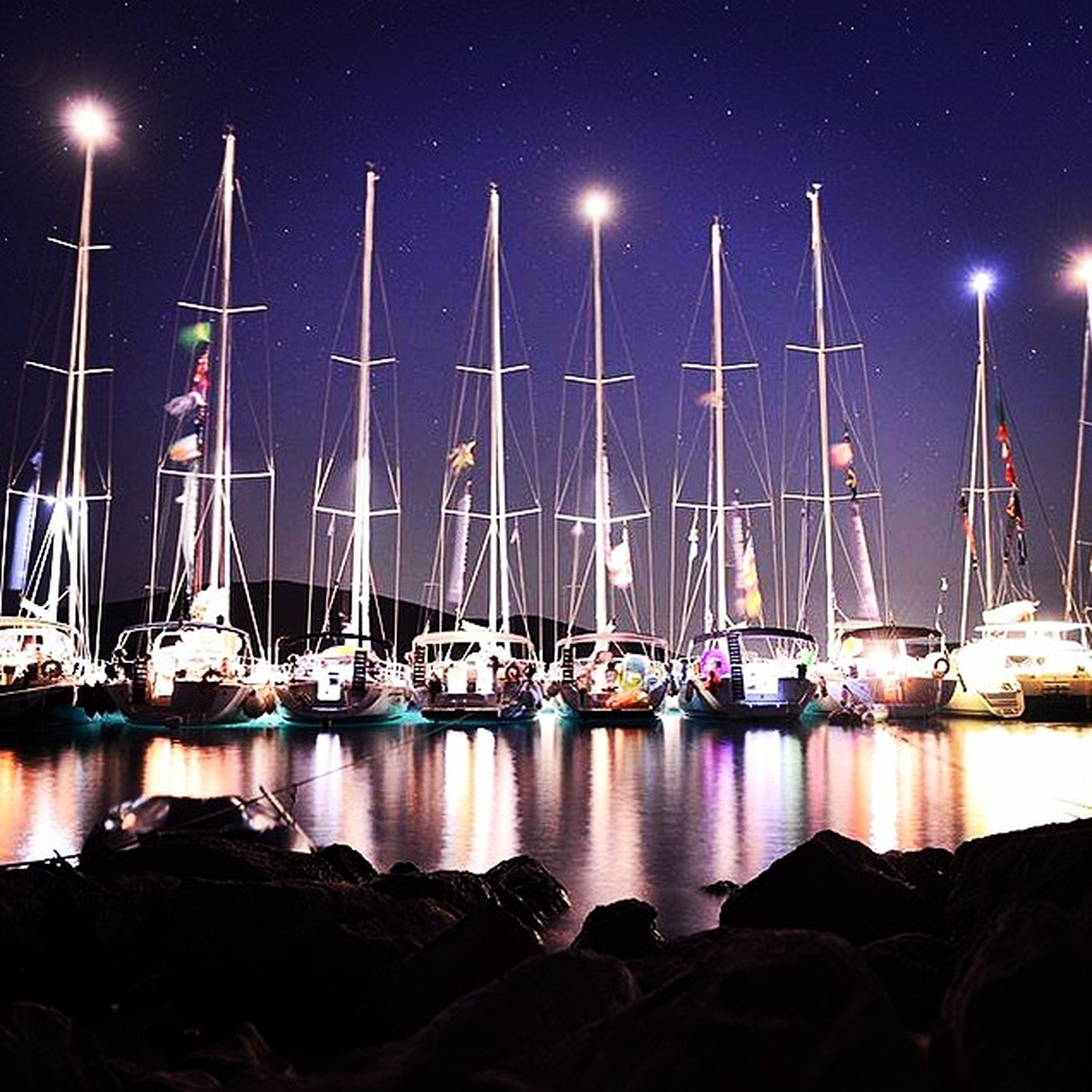 nautical vessel, water, mast, transportation, harbor, night, moored, mode of transport, boat, reflection, sky, sailboat, illuminated, sea, waterfront, outdoors, travel, lake, in a row, no people