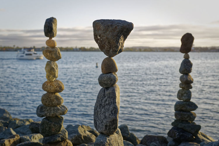 The art of Rock balancing with water and sky in the background Art And Craft ArtWork Calm Geometric Shapes Relaxing Rock Formation Rock Formations Skill  Sky And Clouds A Balance Geometry Hardwork Pebbles Relaxing Moments Rock - Object Rock Balancing Rocks Rocks And Water Sky Stacked Stones Stone Balancing Water Waterfront Zen