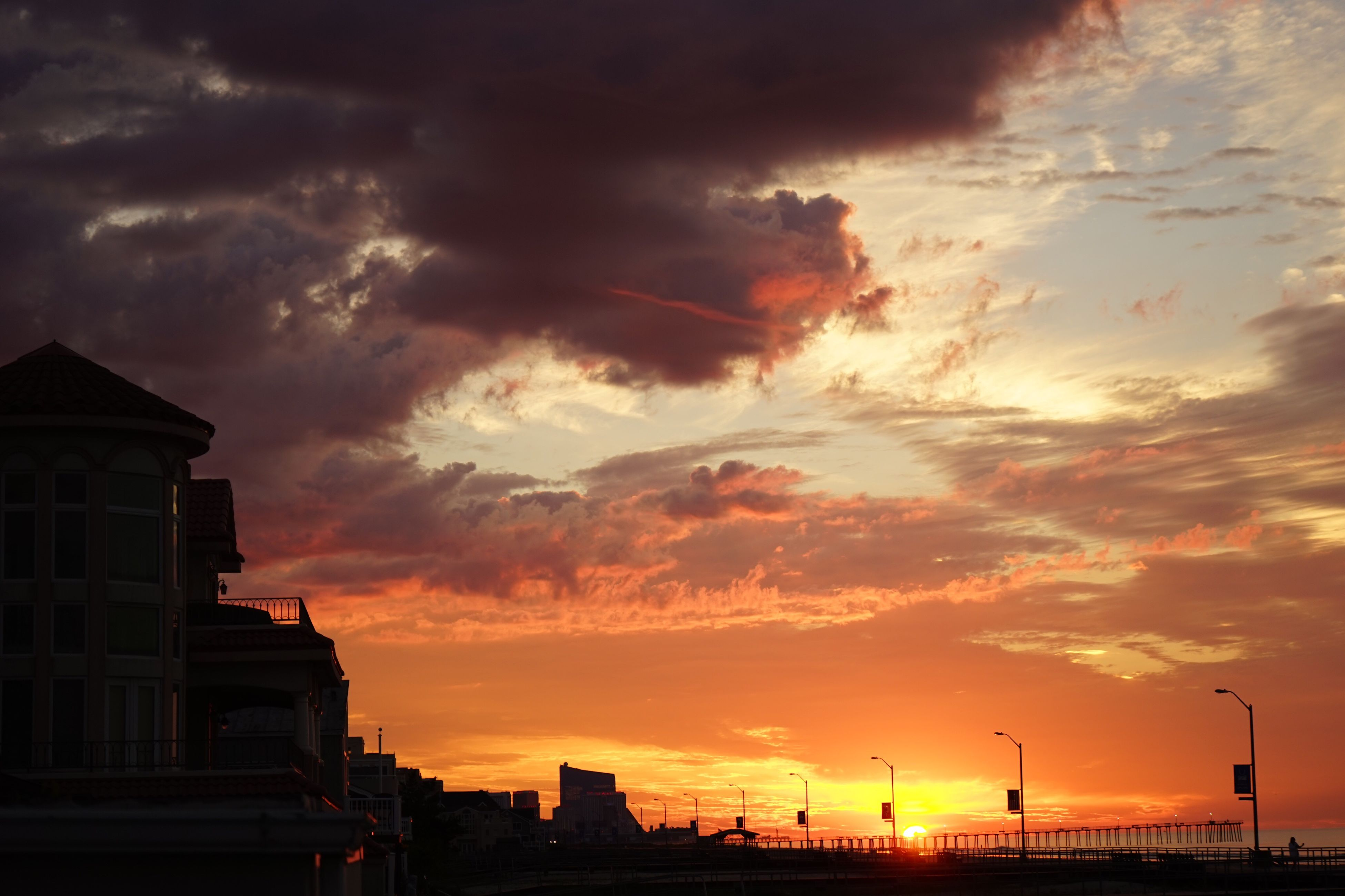 sunset, orange color, architecture, building exterior, built structure, cloud, sky, cloud - sky, sun, scenics, majestic, beauty in nature, tranquility, tranquil scene, nature, dramatic sky, outdoors, storm cloud, cloudy, cloudscape, outline, no people, atmospheric mood, atmosphere, romantic sky, high section, moody sky