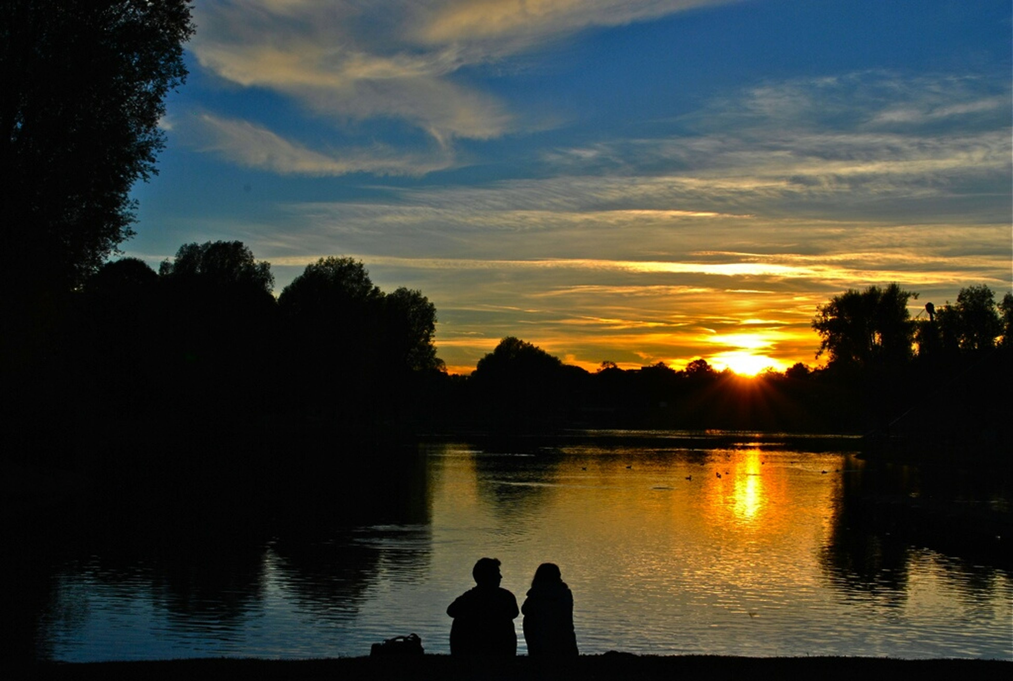 sunset, silhouette, water, lake, reflection, sky, scenics, beauty in nature, tranquil scene, tranquility, tree, nature, idyllic, animal themes, orange color, river, cloud - sky, sun, lakeshore, wildlife
