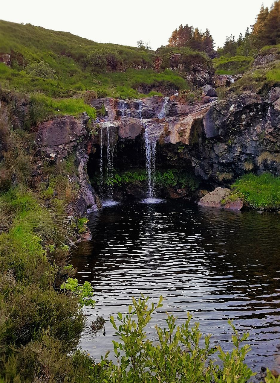 nature, beauty in nature, water, waterfall, scenics, outdoors, rock - object, motion, tranquil scene, day, tree, river, no people, green color, tranquility, plant, sky, grass, power in nature