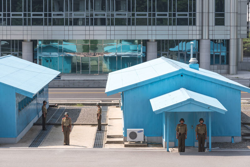 """The Joint Security Area (JSA) is the only portion of the Korean Demilitarized Zone (DMZ) where North and South Korean forces stand face-to-face. It is often called the """"Truce Village"""" in both the media. This picture was taken from the North Korea side Communism DMZ, North Korea, South Korea DPRK DPRKorea JSA Korean Korean War North Korea Soldier Army Army Soldier Blue House Building Exterior Day Dmz Full Length Kaesong Separation Socialism Standing War"""