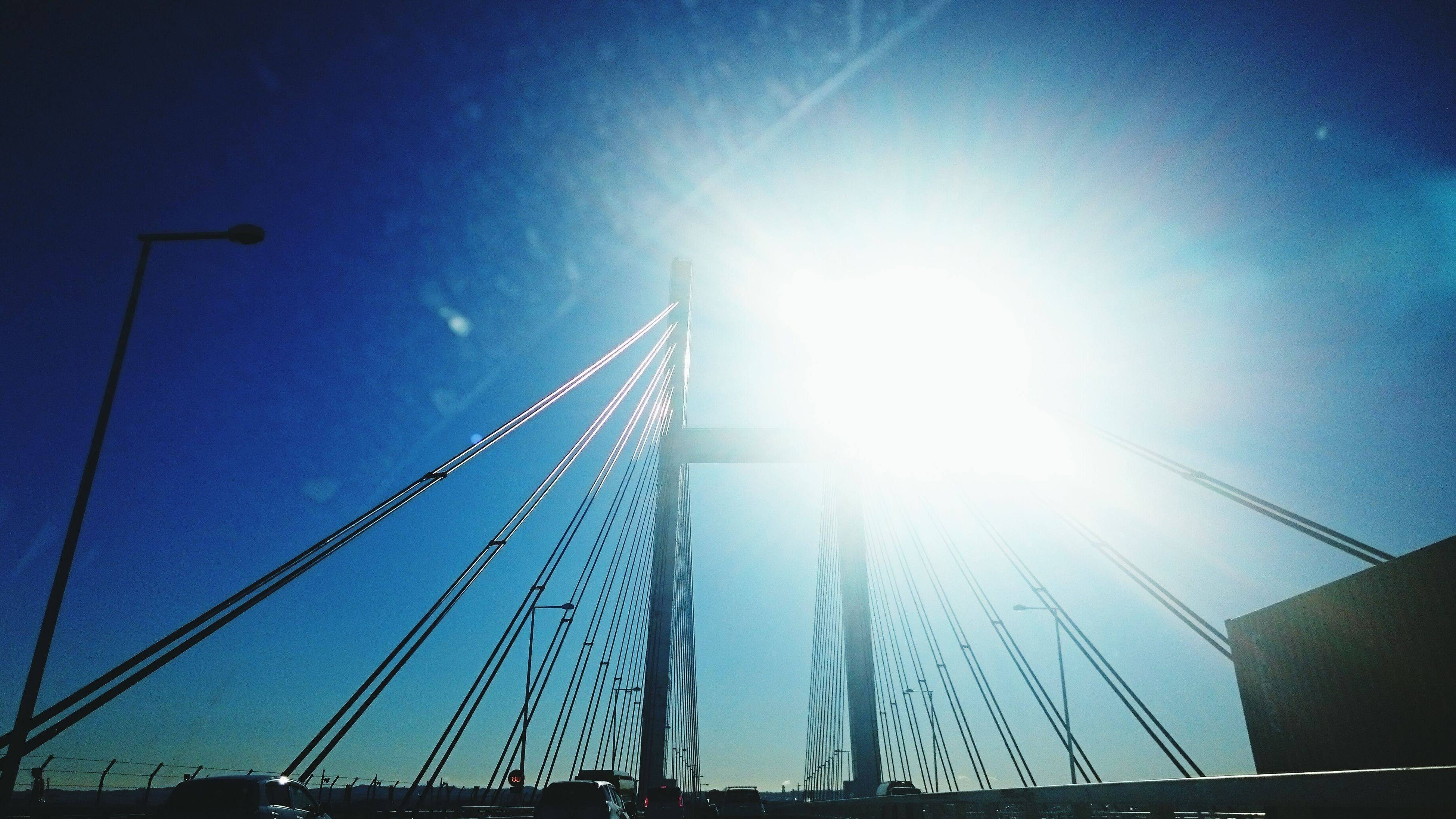 built structure, architecture, sunbeam, sky, low angle view, lens flare, sunlight, sun, connection, blue, building exterior, transportation, suspension bridge, bridge - man made structure, no people, outdoors, city, day