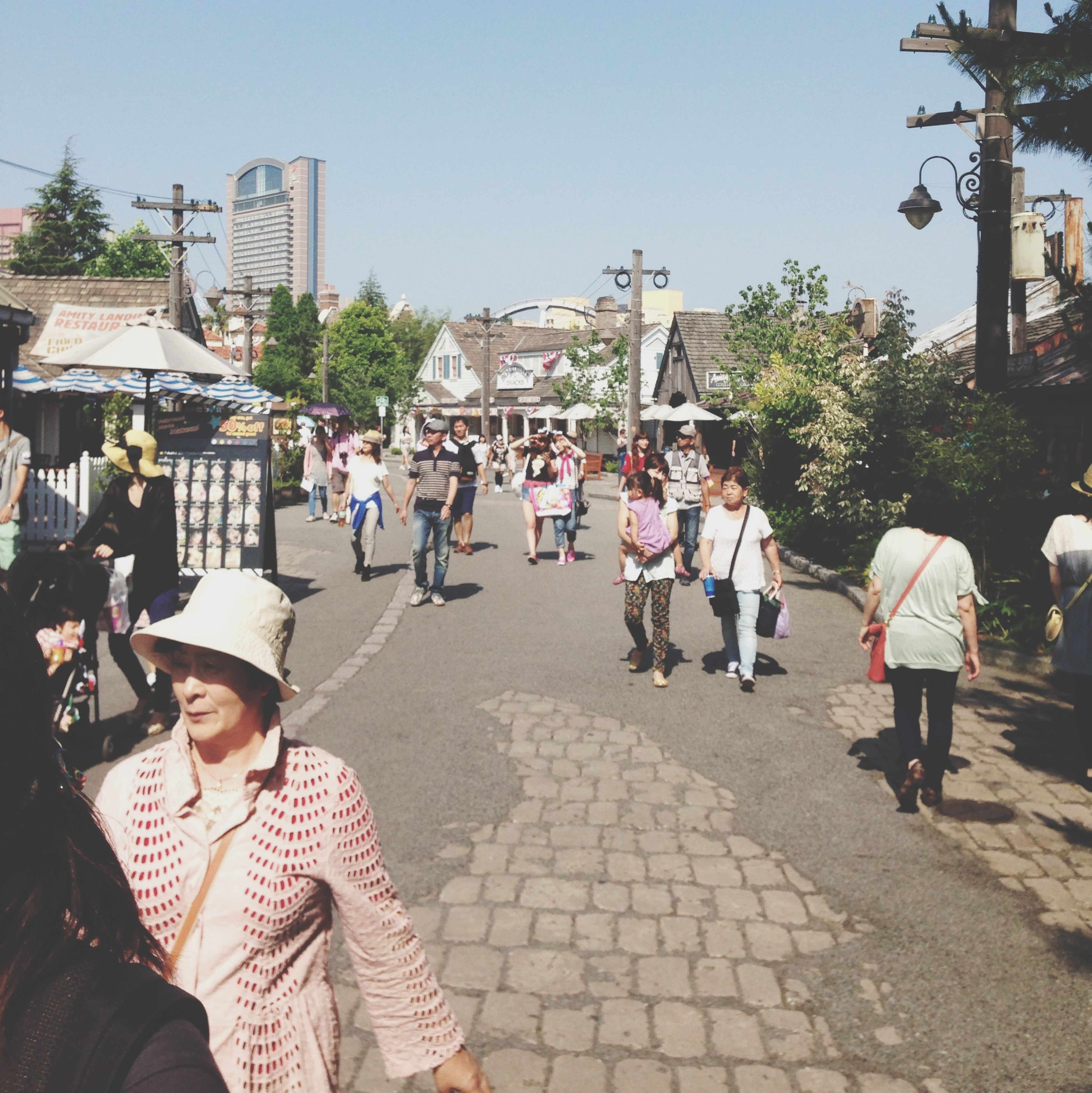 building exterior, architecture, built structure, lifestyles, large group of people, person, men, leisure activity, city, street, cobblestone, clear sky, walking, togetherness, casual clothing, city life, sunlight, mixed age range, outdoors