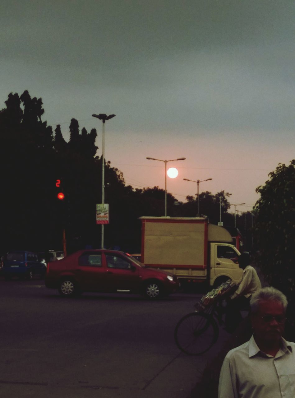 car, transportation, land vehicle, sunset, mode of transport, illuminated, men, real people, outdoors, street light, one person, road, tree, sky, night, building exterior, city, architecture, people