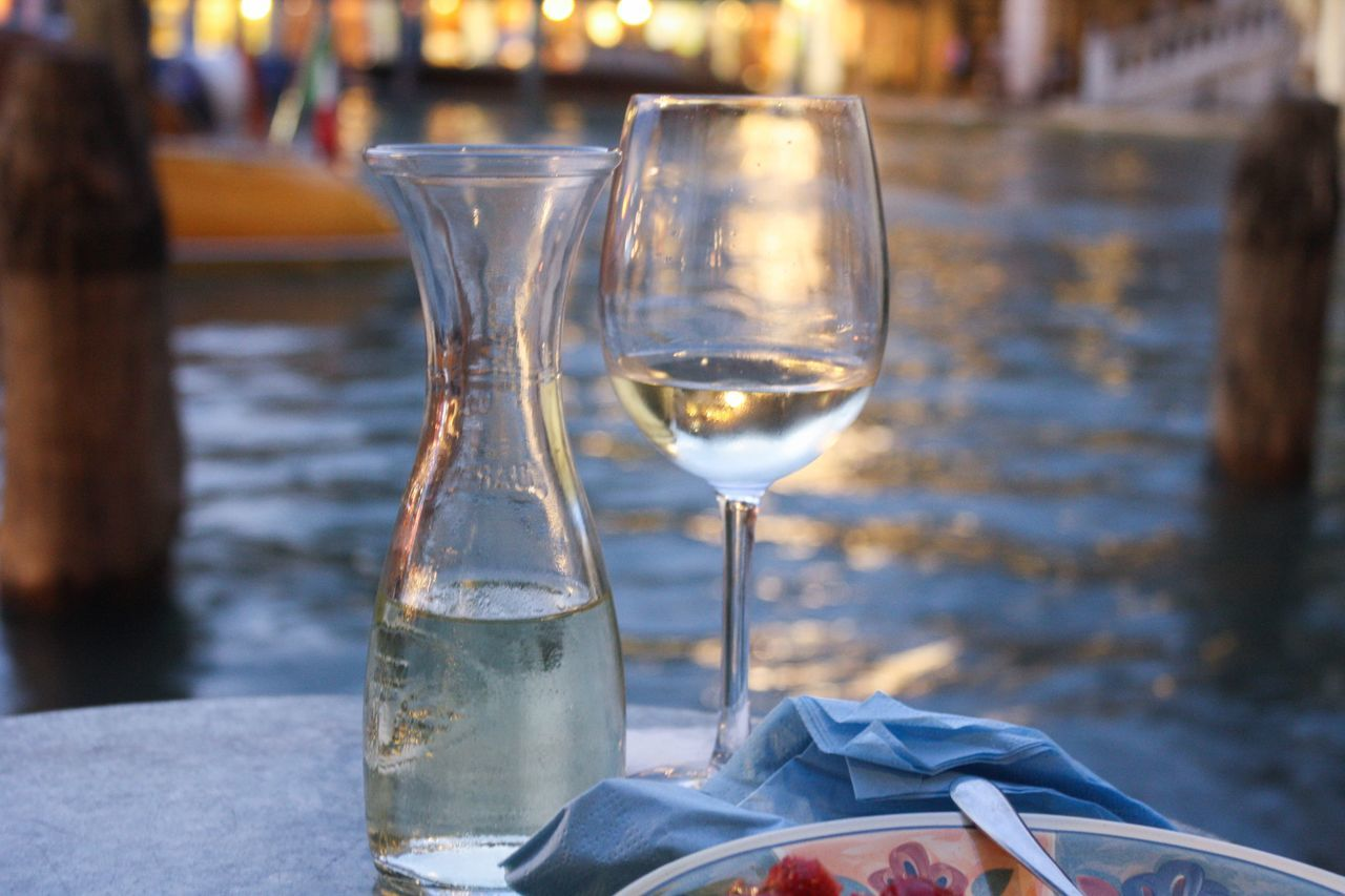 wineglass, wine, drink, food and drink, drinking glass, focus on foreground, alcohol, table, incidental people, refreshment, close-up, outdoors, freshness, day, food, one person