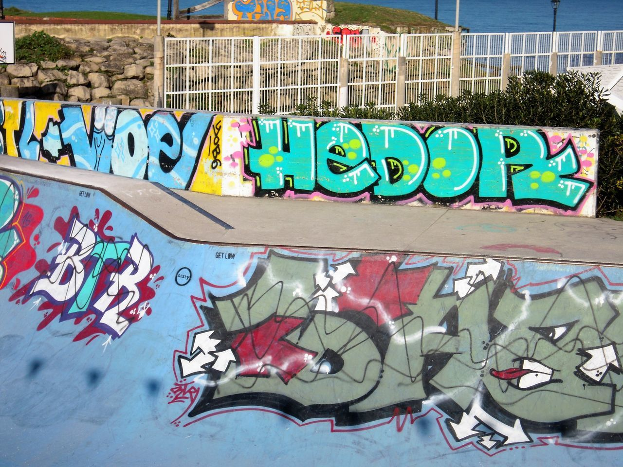 graffiti, text, creativity, art and craft, street art, western script, wall - building feature, multi colored, day, built structure, building exterior, architecture, outdoors, communication, no people, skateboard park