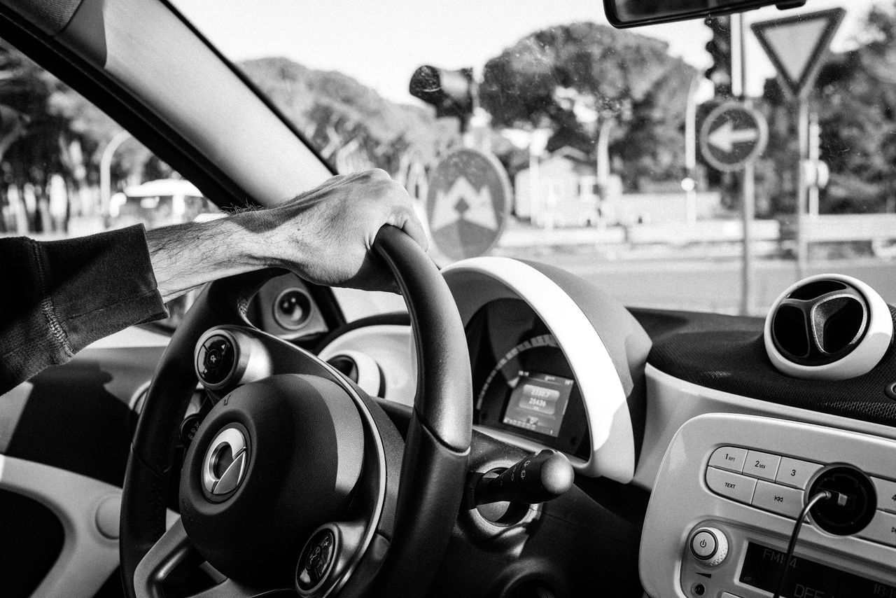 Black And White Car Car Interior City Close-up Control Panel Dashboard Day Human Body Part Human Hand Land Vehicle Mode Of Transport One Person Outdoors People Real People Speedometer Steering Wheel Technology Transportation Vehicle Interior Let's Go Together