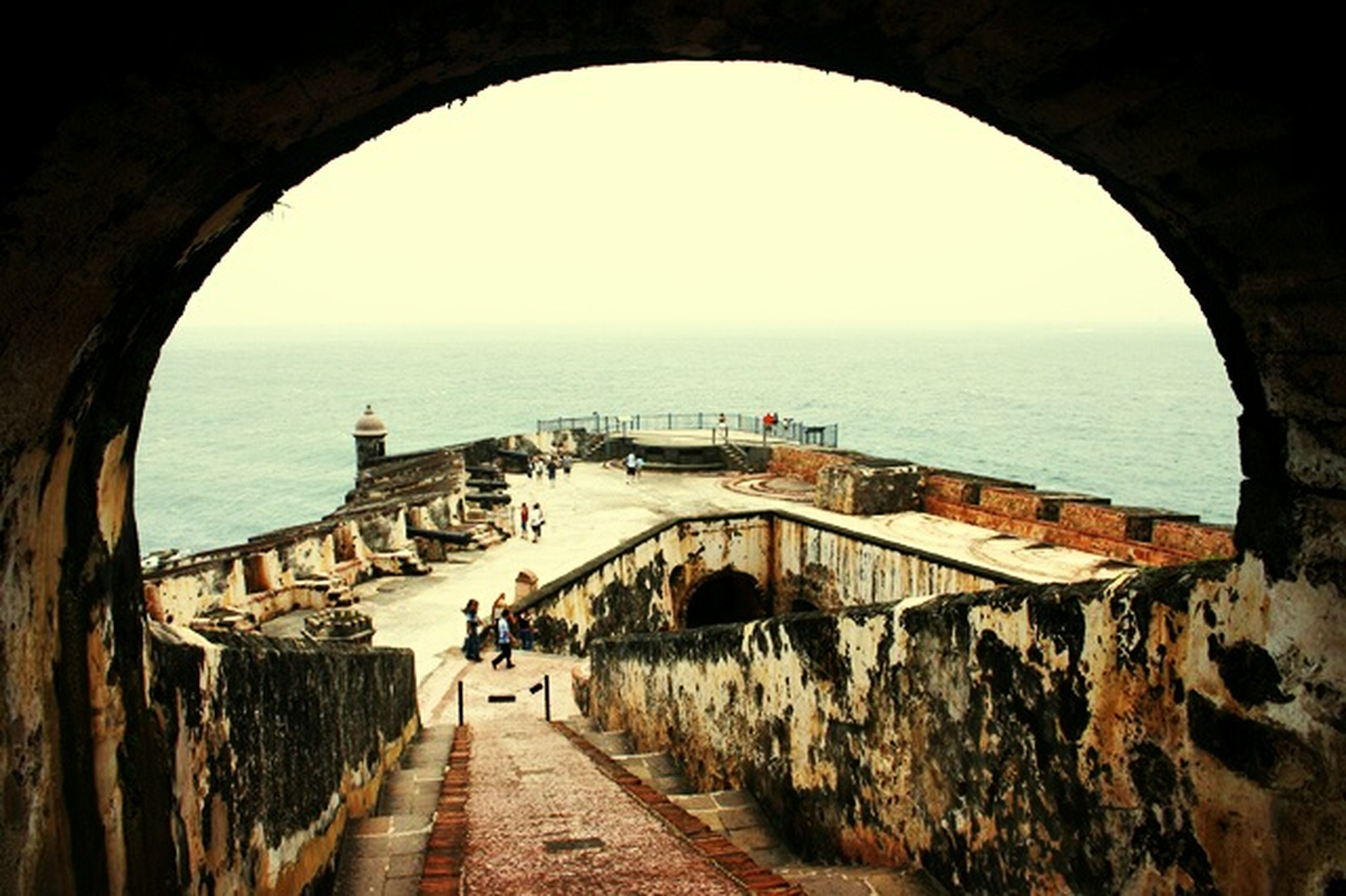 sea, horizon over water, the way forward, built structure, architecture, arch, water, indoors, incidental people, narrow, clear sky, sky, archway, diminishing perspective, blue, tourism, railing, beach, day, sunlight