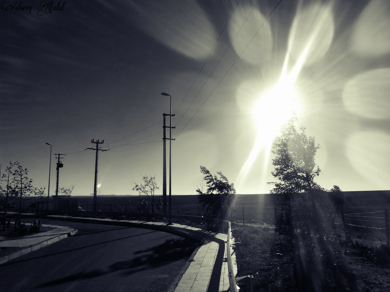 sunbeam, lens flare, sky, transportation, road, sun, sunlight, electricity pylon, cloud - sky, car, the way forward, outdoors, nature, no people, street light, day, tree, beauty in nature