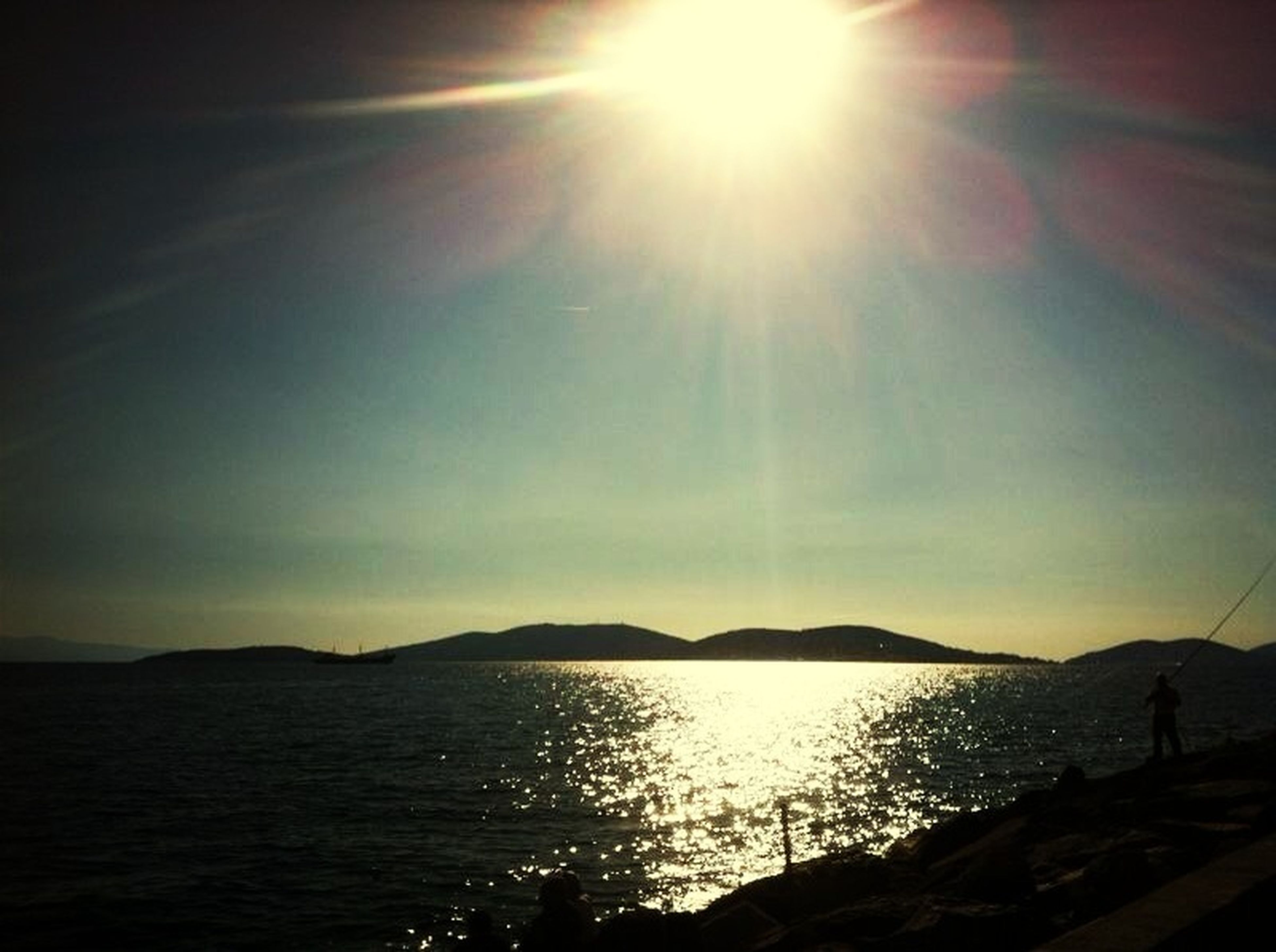 sun, water, sunbeam, tranquil scene, scenics, tranquility, sunlight, sea, beauty in nature, mountain, lens flare, sky, nature, mountain range, idyllic, reflection, sunset, bright, silhouette, outdoors