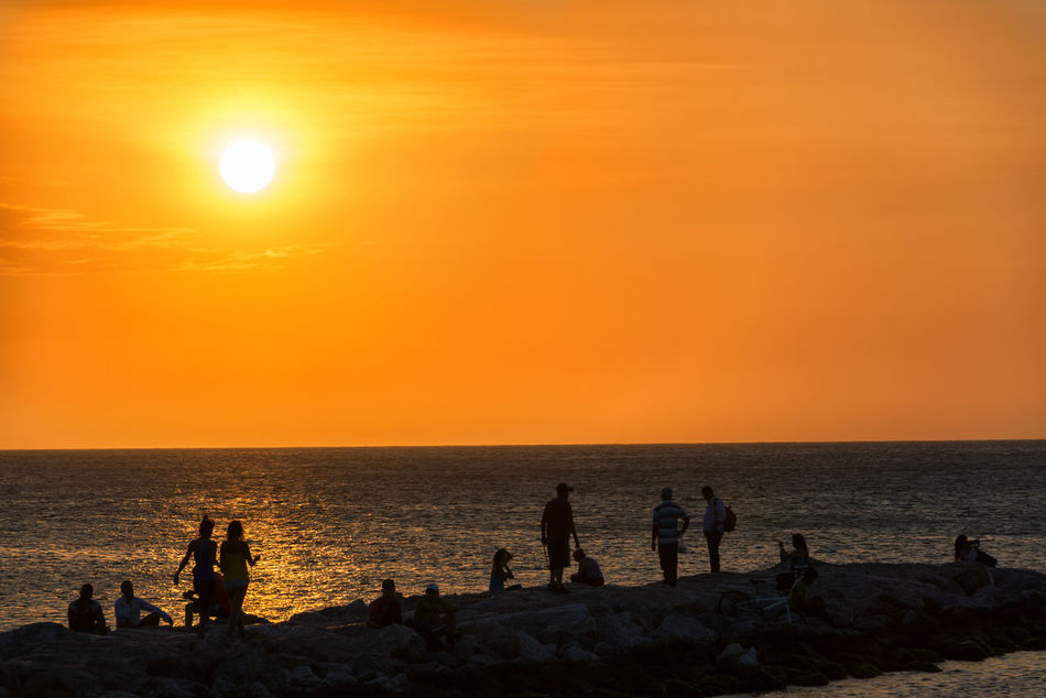 Silhouettes of people enjoying a beach a sunset in Santa Marta, Colombia Beach Beautiful Calm Caribbean Coast Coastline Coconut Colombia Day Holiday Hot Idyllic Island Landscape Nature Nature Nobody Ocean Outdoors Palm Paradise Santa Marta Sky Sun Sunset