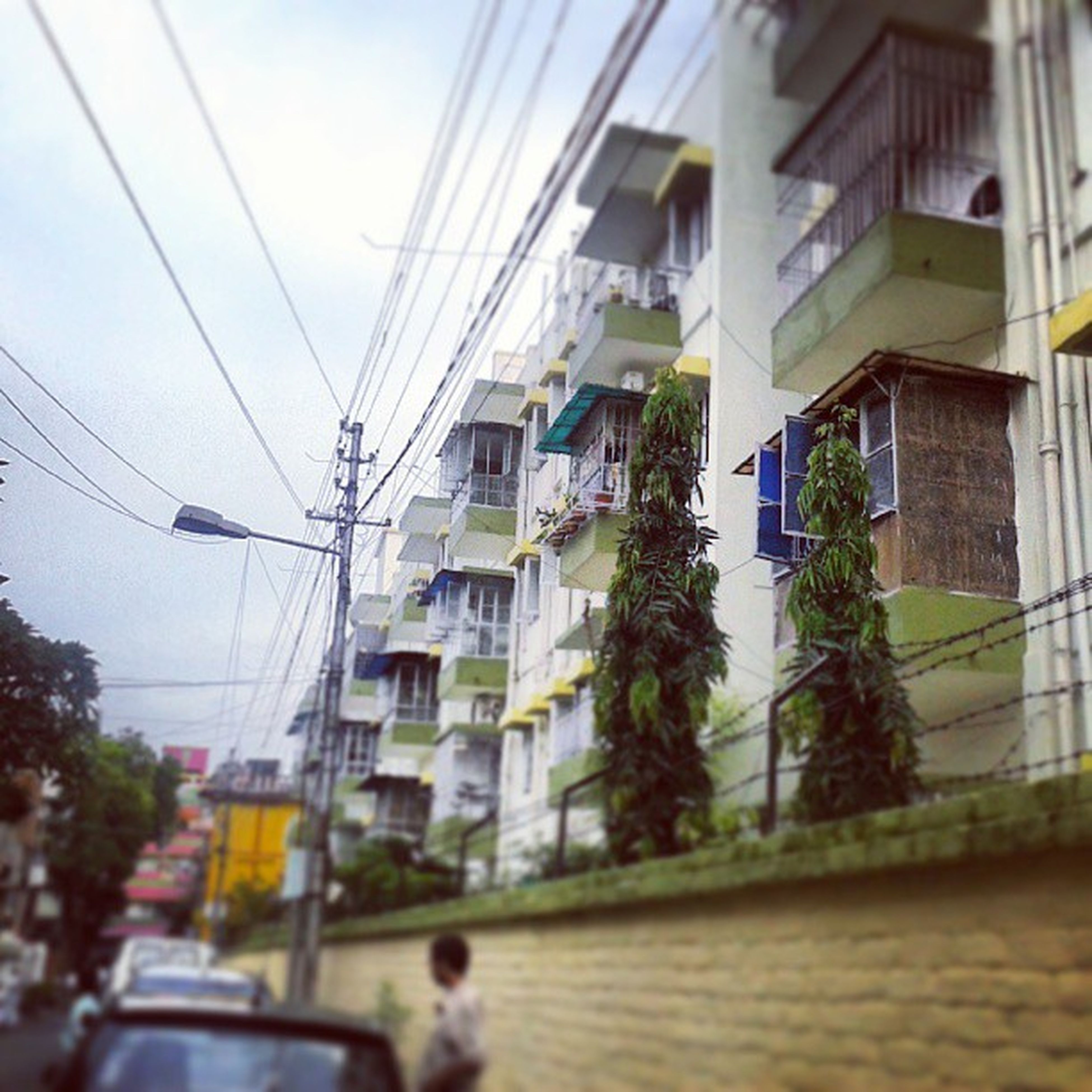 building exterior, architecture, built structure, power line, street, transportation, city, cable, residential building, road, building, residential structure, electricity pylon, day, window, tree, car, city life, outdoors, sky