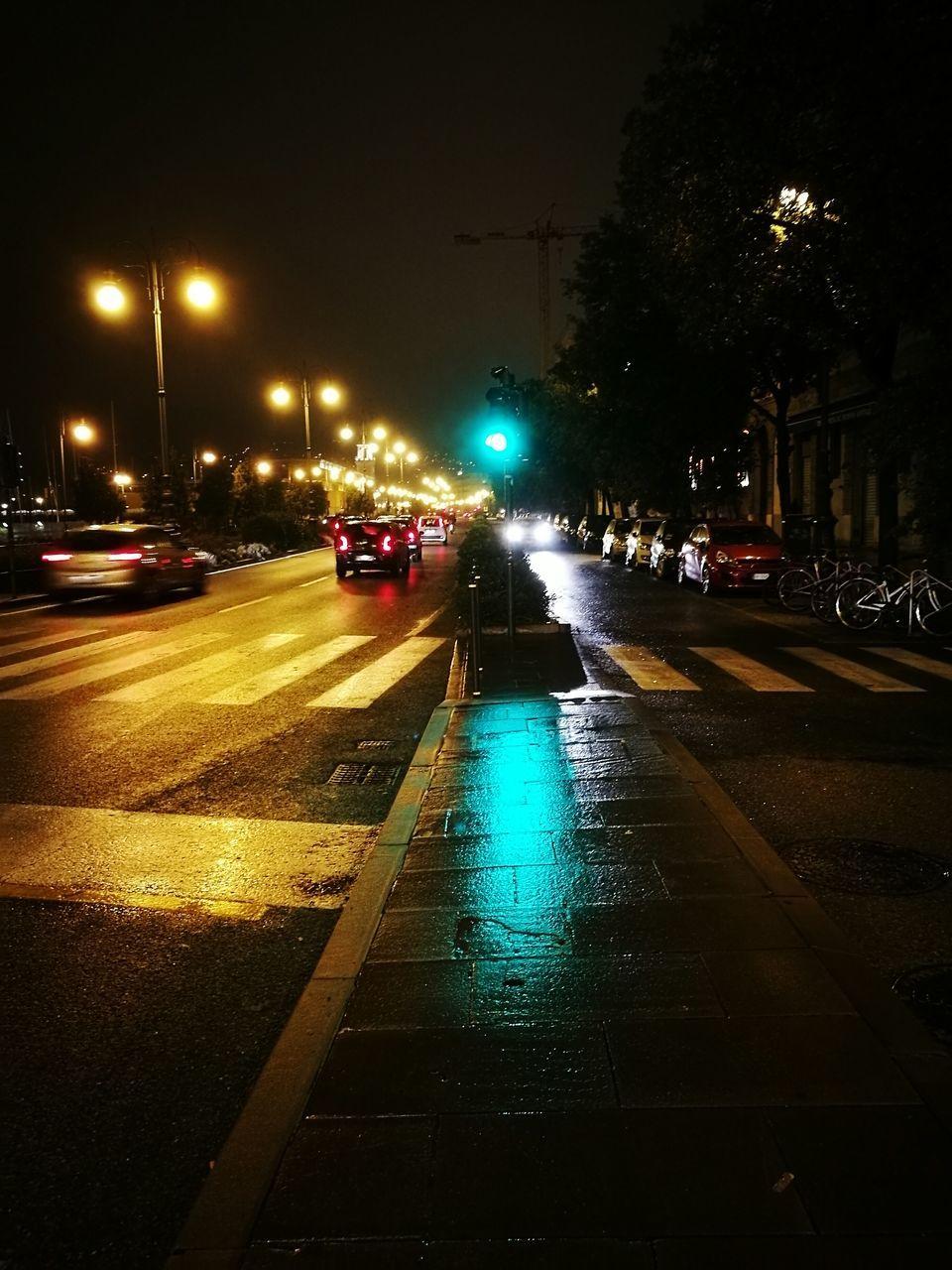 illuminated, night, transportation, street, car, city, road, street light, land vehicle, wet, outdoors, architecture, building exterior, no people, sky