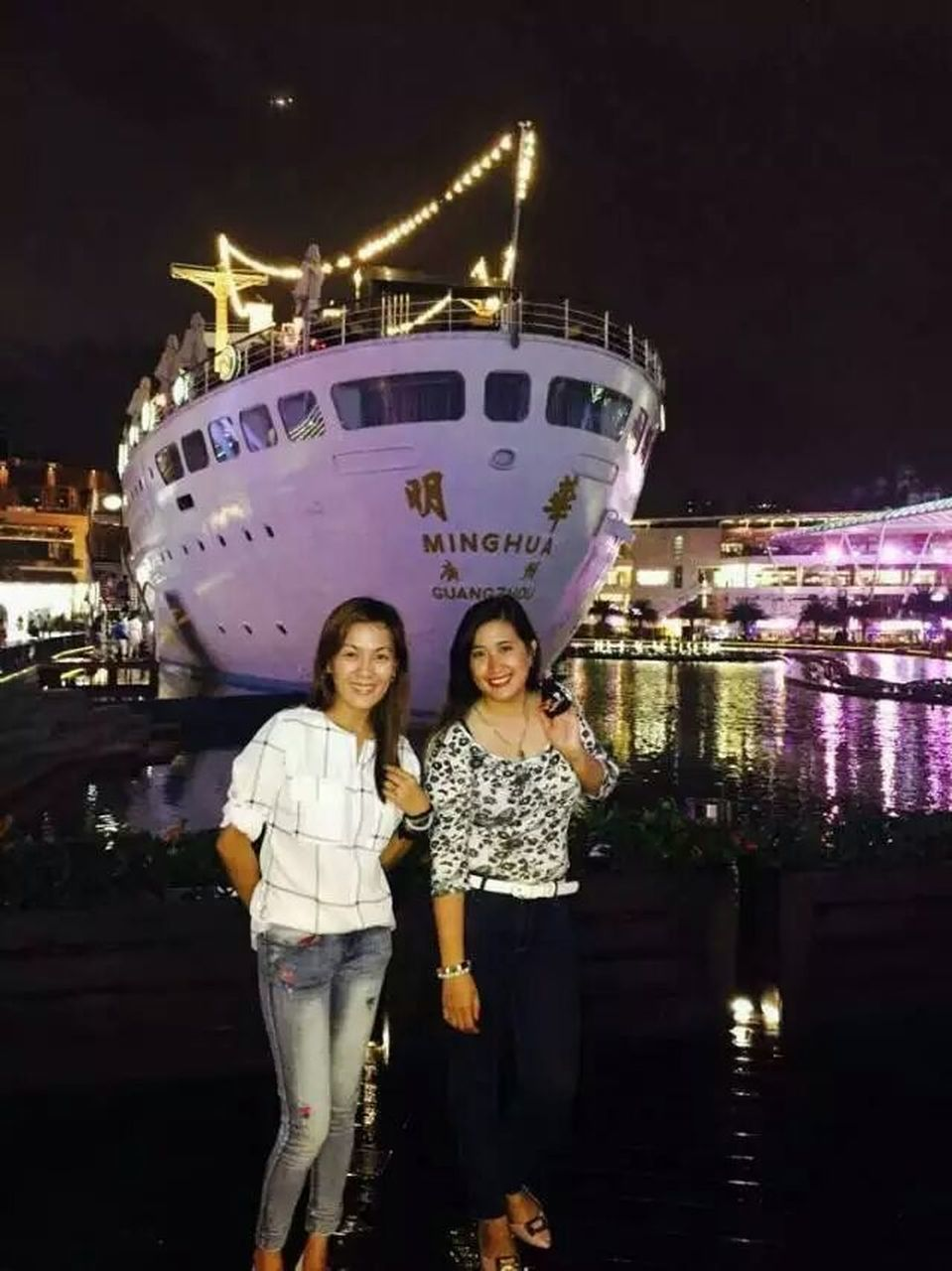 night, two people, standing, portrait, looking at camera, togetherness, girls, illuminated, front view, building exterior, smiling, leisure activity, real people, lifestyles, outdoors, architecture, happiness, ferris wheel, built structure, full length, young women, sky, childhood, young adult, friendship, city, people