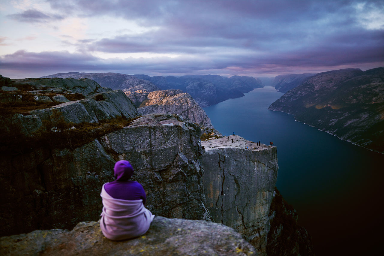 A girl is sitting enjoying the last light over Pulpit rock in Norway Adventure Cliff Fjord High Landscape Lysefjorden Nature Norge Norgeibilder Norway Norway🇳🇴 Outdoors Pink Preikestolen Pulpitrock Purple Summit Sundown Sunset Travel Visitnorway
