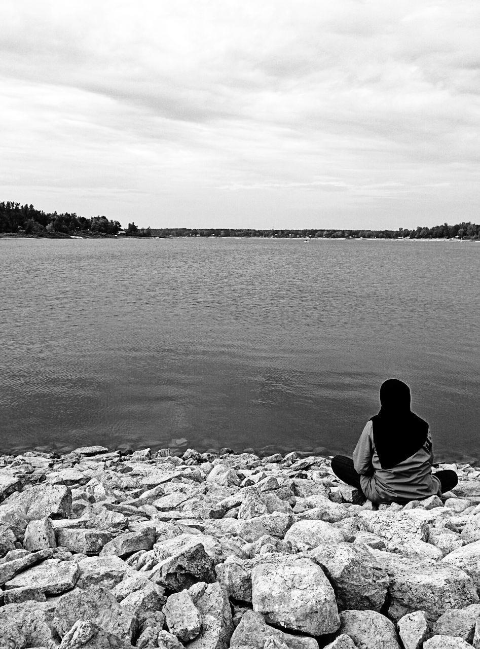Rear View of Woman Sitting On Rocks At Lake Shore