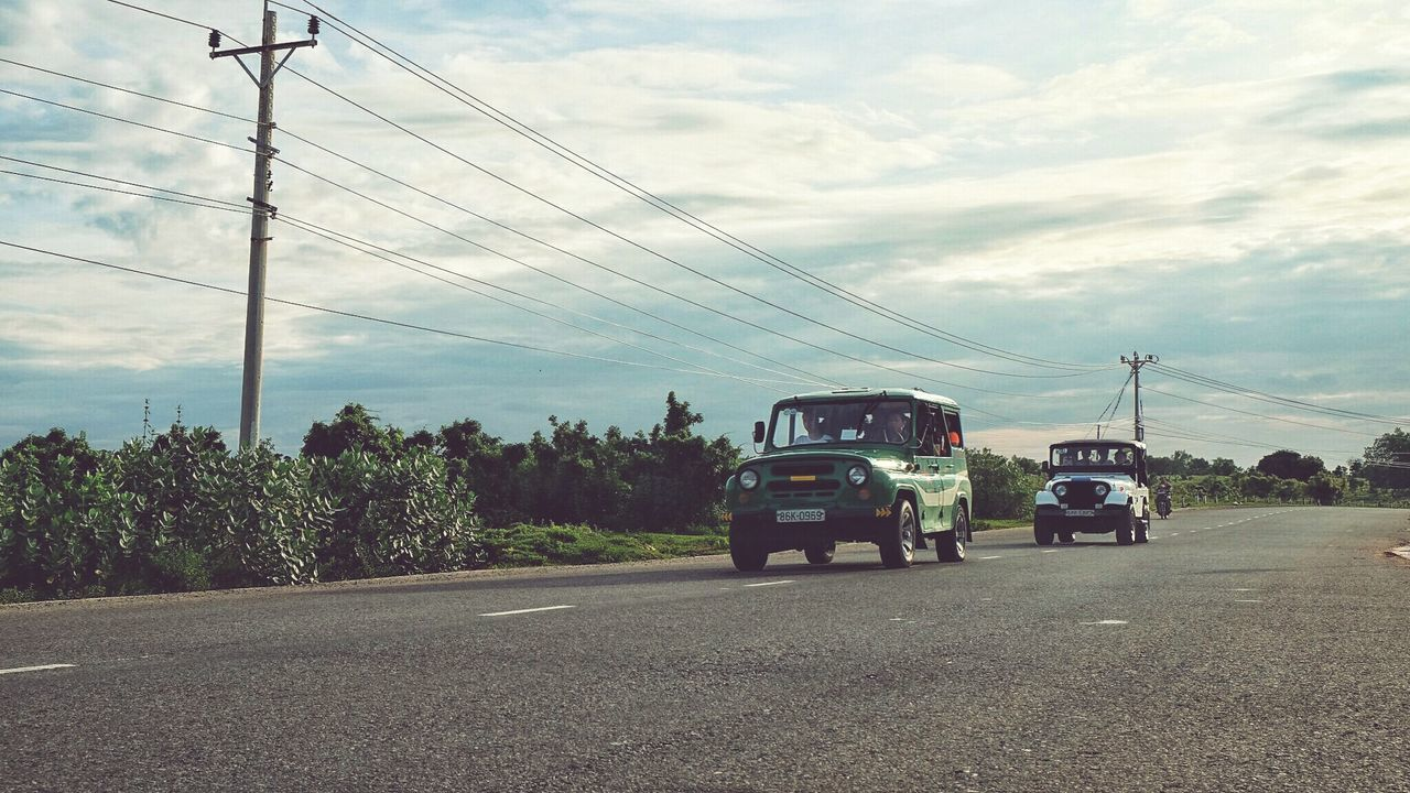 transportation, mode of transport, cable, land vehicle, car, sky, cloud - sky, power line, electricity pylon, road, electricity, power supply, real people, day, fuel and power generation, outdoors, tree, men, nature, technology, telephone line, people