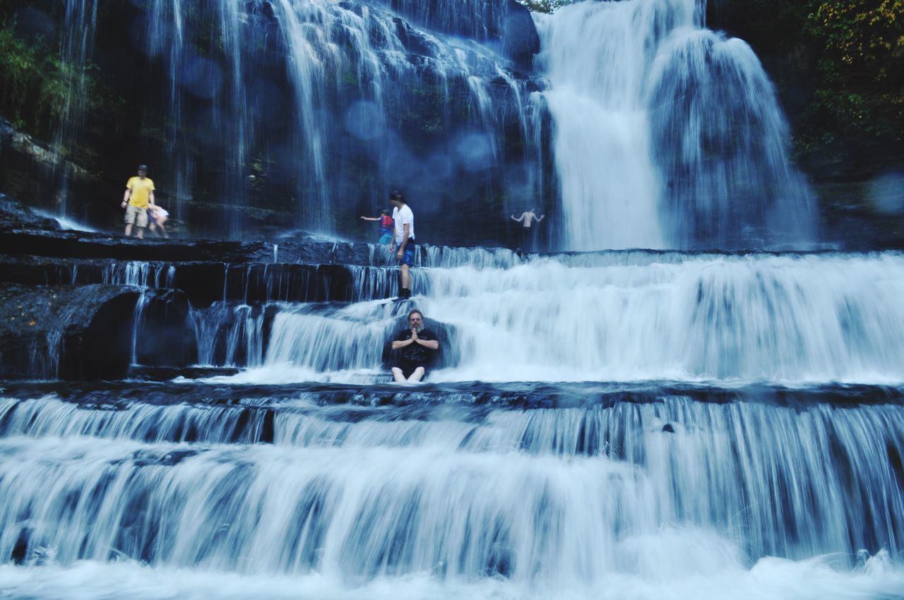 waterfall, motion, water, long exposure, splashing, flowing water, blurred motion, nature, outdoors, rock - object, running water, day, men, vacations, adventure, hot spring, river, spraying, real people, travel destinations, beauty in nature, large group of people, people