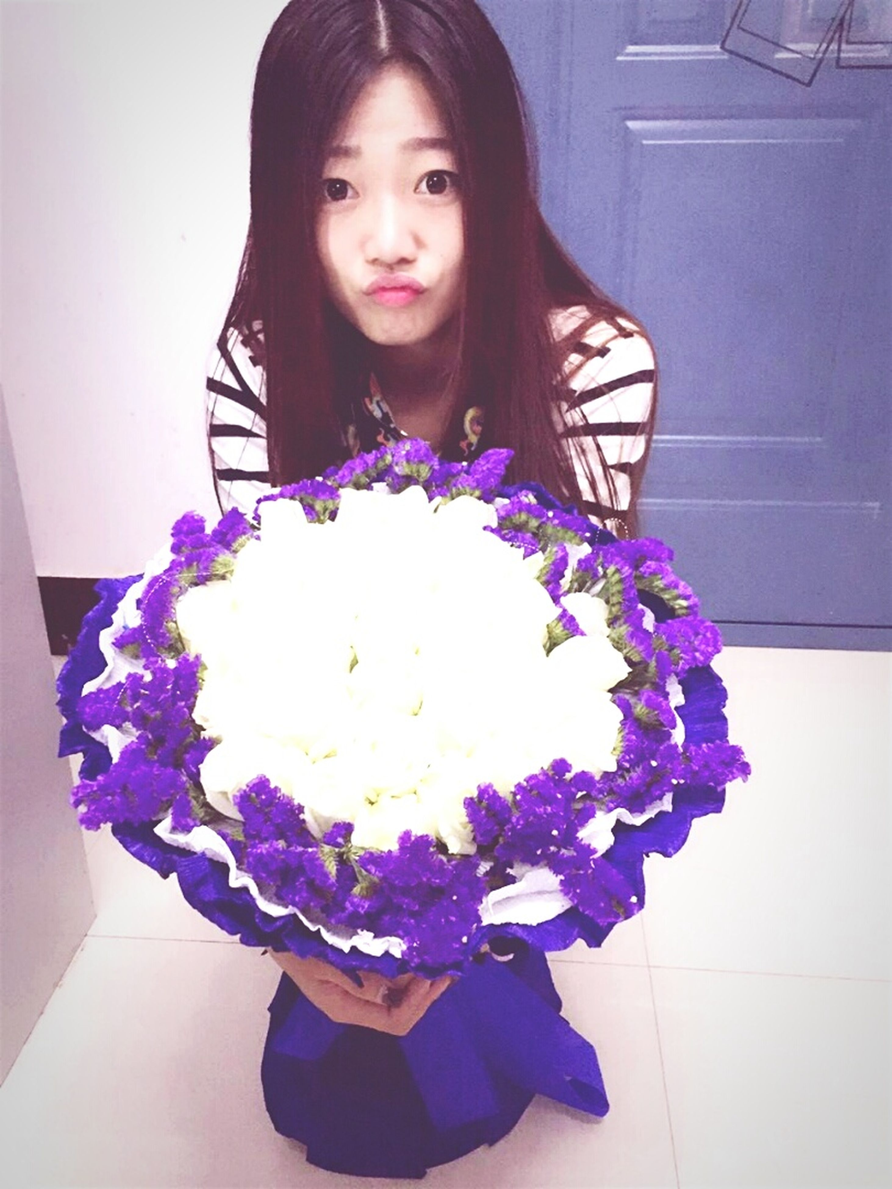 indoors, flower, front view, home interior, bouquet, lifestyles, casual clothing, purple, person, leisure activity, holding, fragility, wall - building feature, decoration, freshness, high angle view, looking at camera, portrait