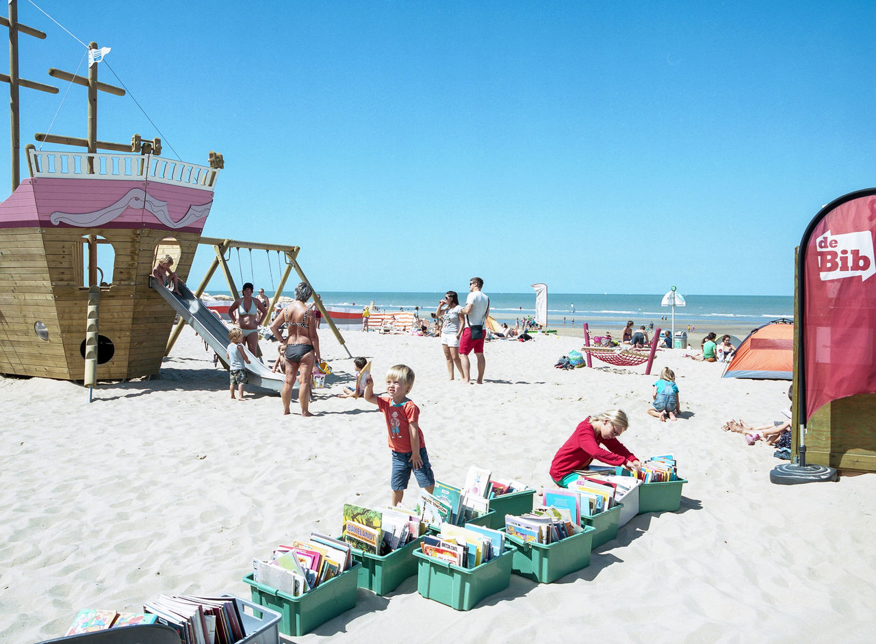 beach, sand, clear sky, real people, sea, large group of people, day, vacations, sunlight, men, leisure activity, nature, outdoors, lifestyles, summer, water, women, horizon over water, sky, beauty in nature, people