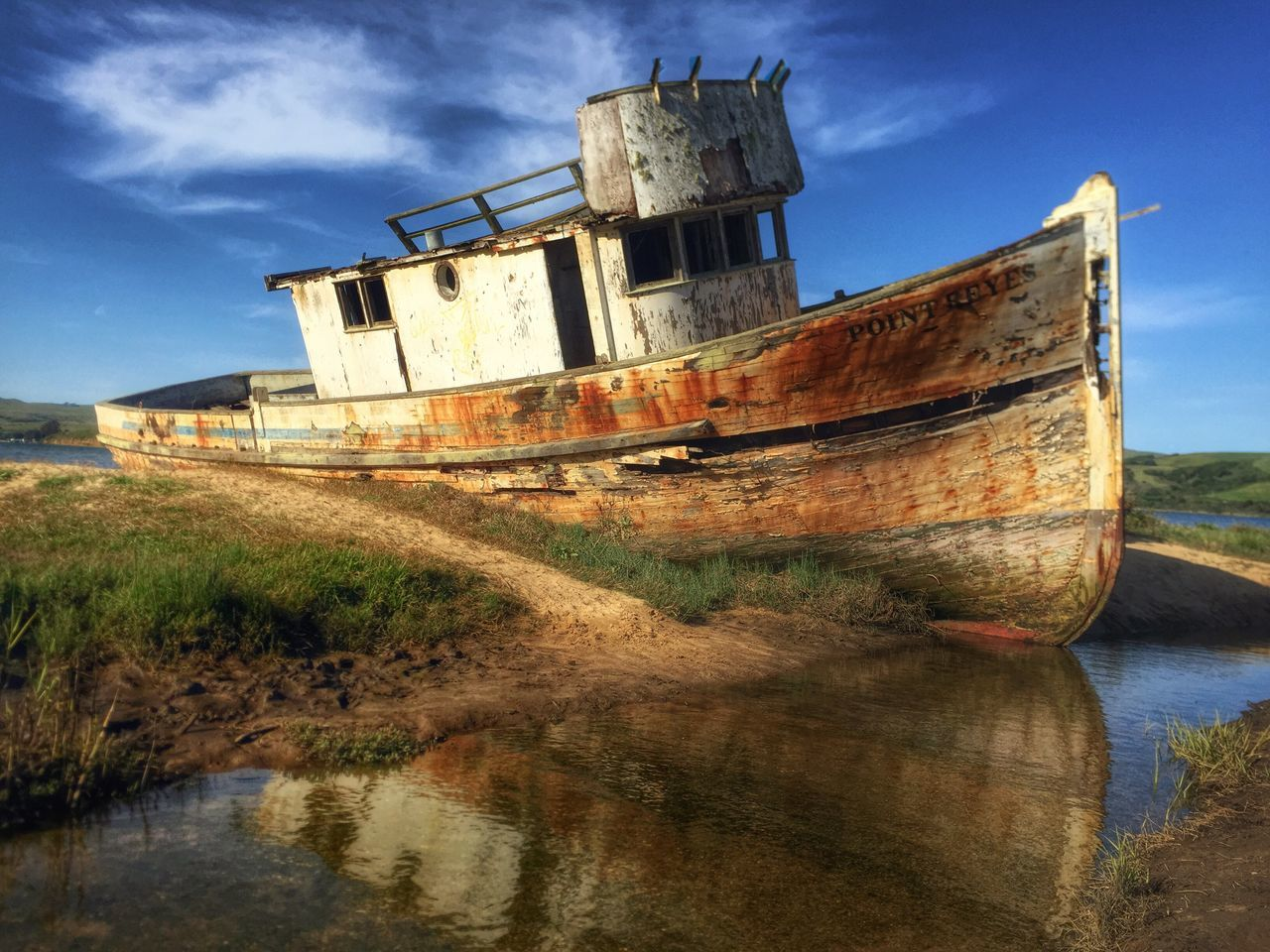 Abandoned Boat On Riverbank Against Blue Sky