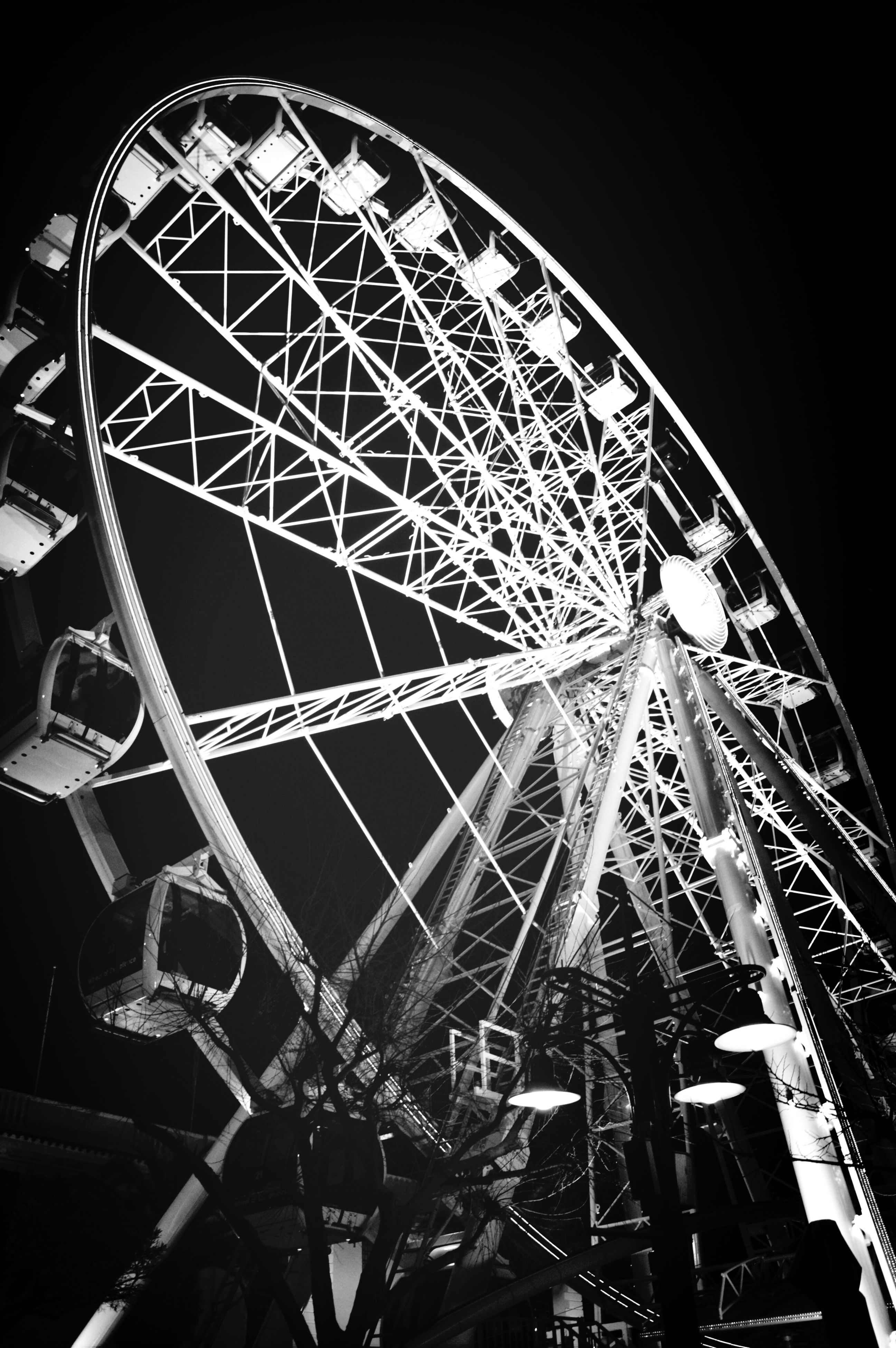ferris wheel, low angle view, amusement park ride, amusement park, arts culture and entertainment, built structure, architecture, night, clear sky, illuminated, sky, metal, building exterior, city, tall - high, no people, outdoors, circle, travel destinations, capital cities